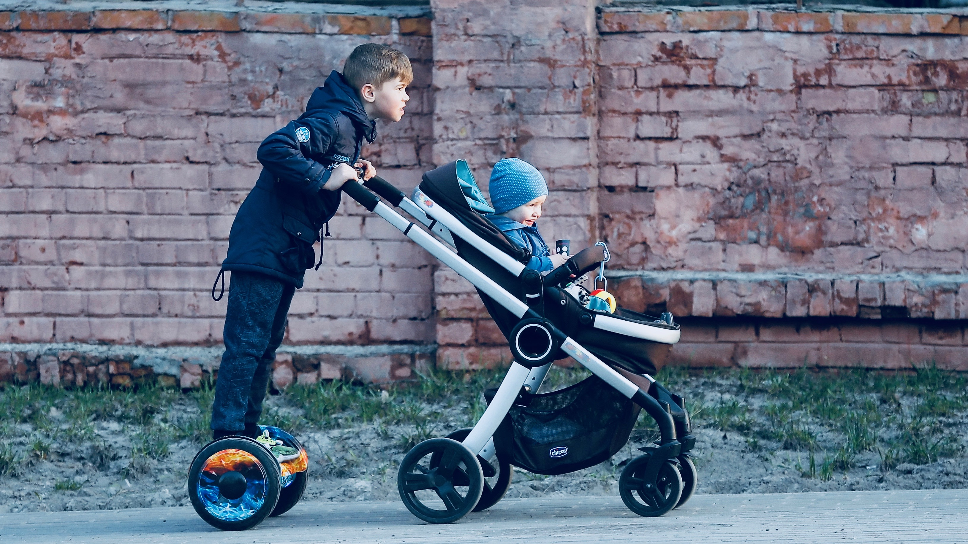 A young boy carries a baby carriage with his brother as he rides a gyroscooter in downtown Kiev, Ukraine,