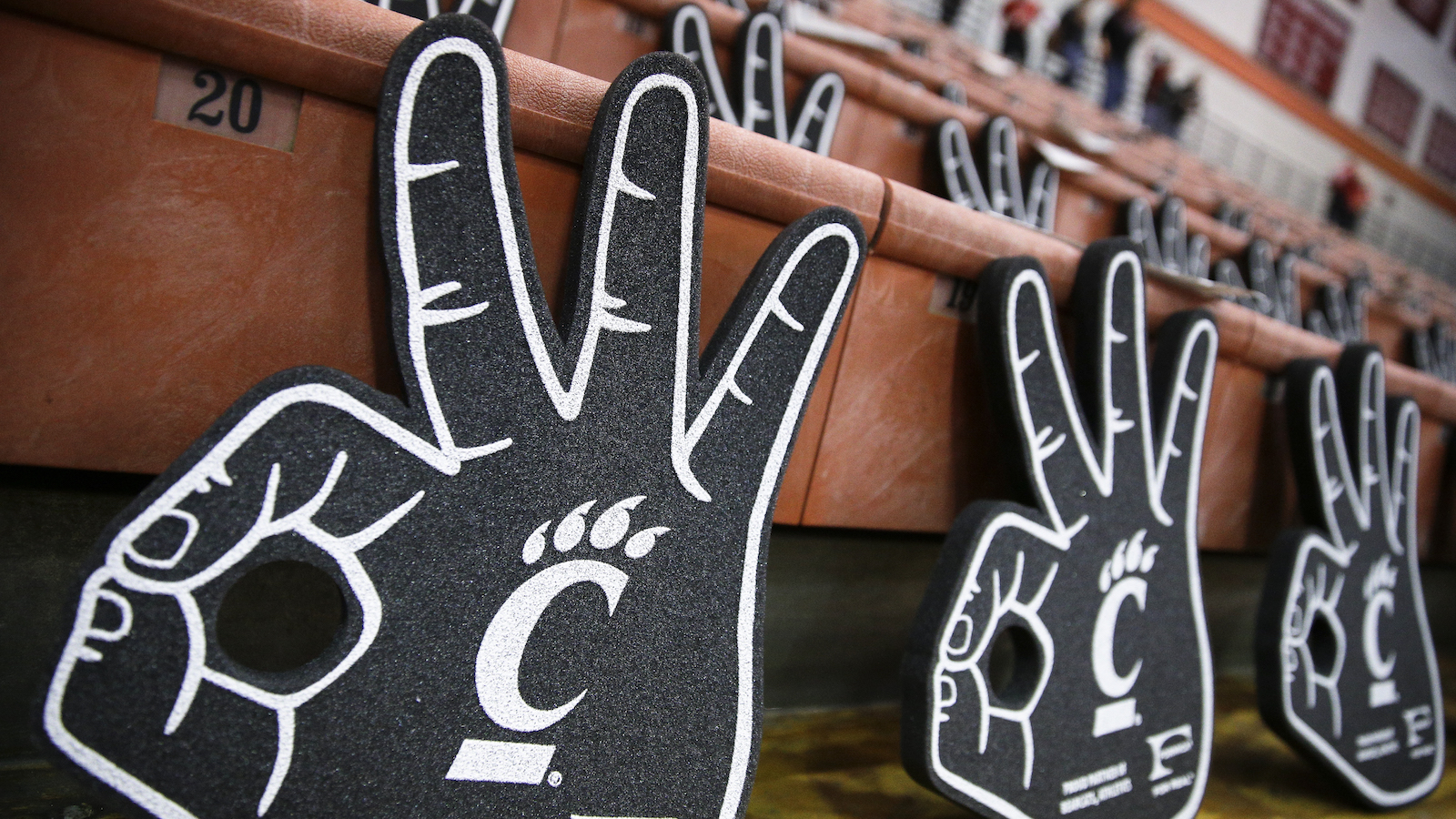 Foam three-point goal fingers representing the Cincinnati Bearcats rest on the bleachers before the first half of an NCAA college basketball game against SMU, Sunday, March 6, 2016, in Cincinnati. (AP Photo/John Minchillo)