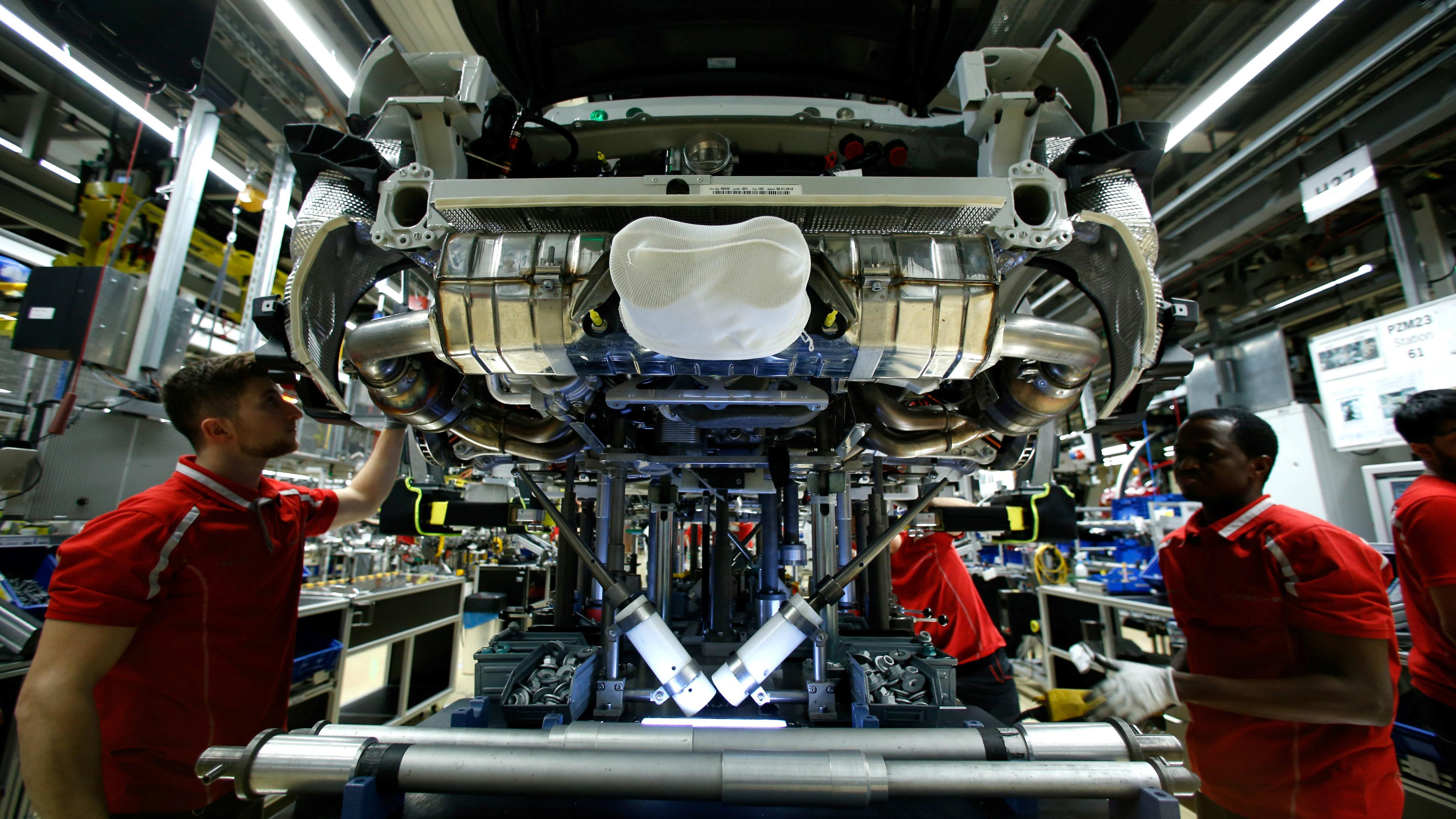 Employees of German car manufacturer Porsche work on a sports car at the Porsche factory in Stuttgart-Zuffenhausen, Germany