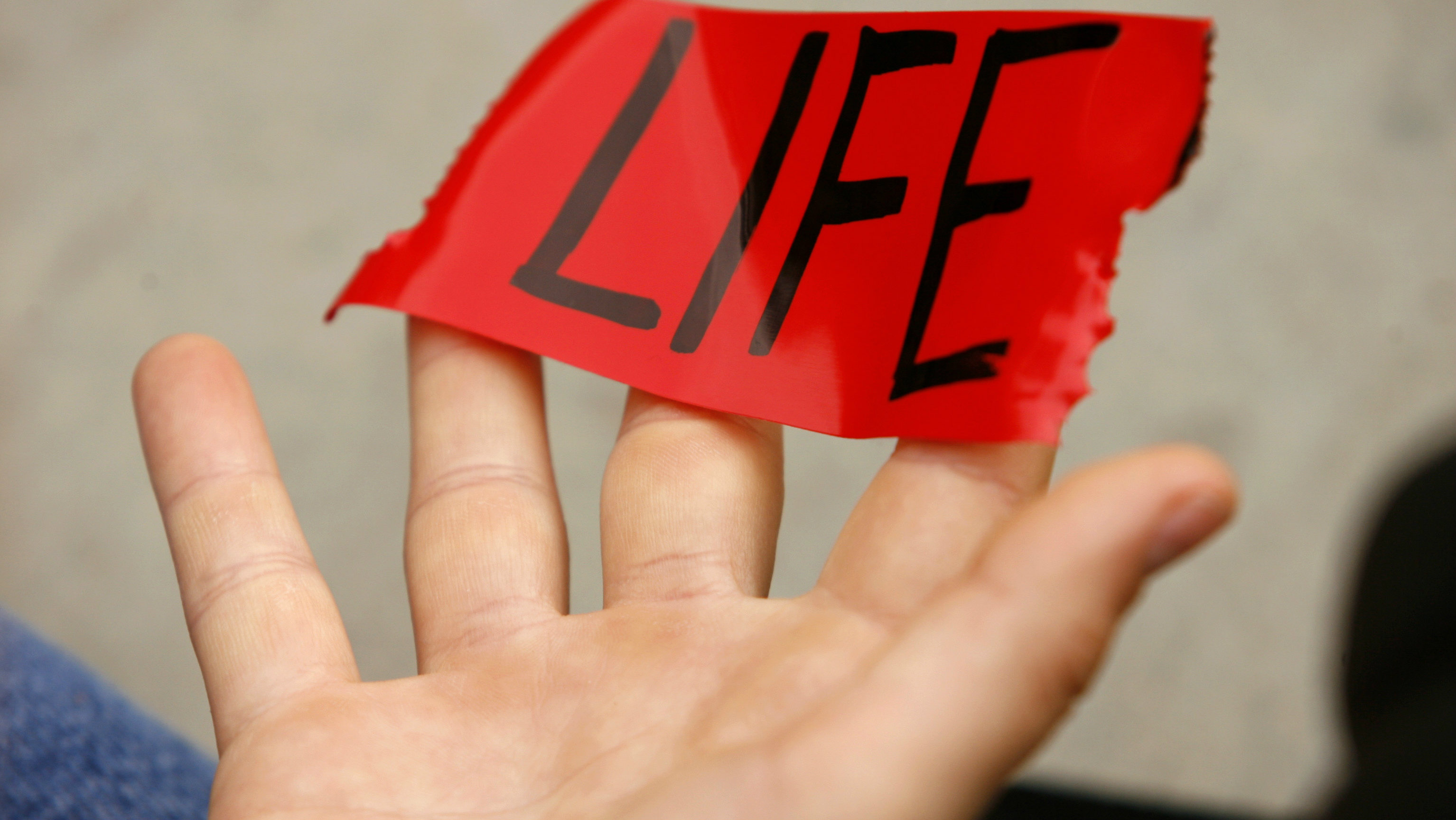 "A pro-life demonstrator holds up piece of tape with the word ""life"" outside the Supreme Court in Washington October 6, 2008. Amid a presidential race that may decide its future direction, the Supreme Court began a new term today with cases about tobacco company lawsuits, protecting whales from Navy sonar and a government crackdown on dirty words on television."