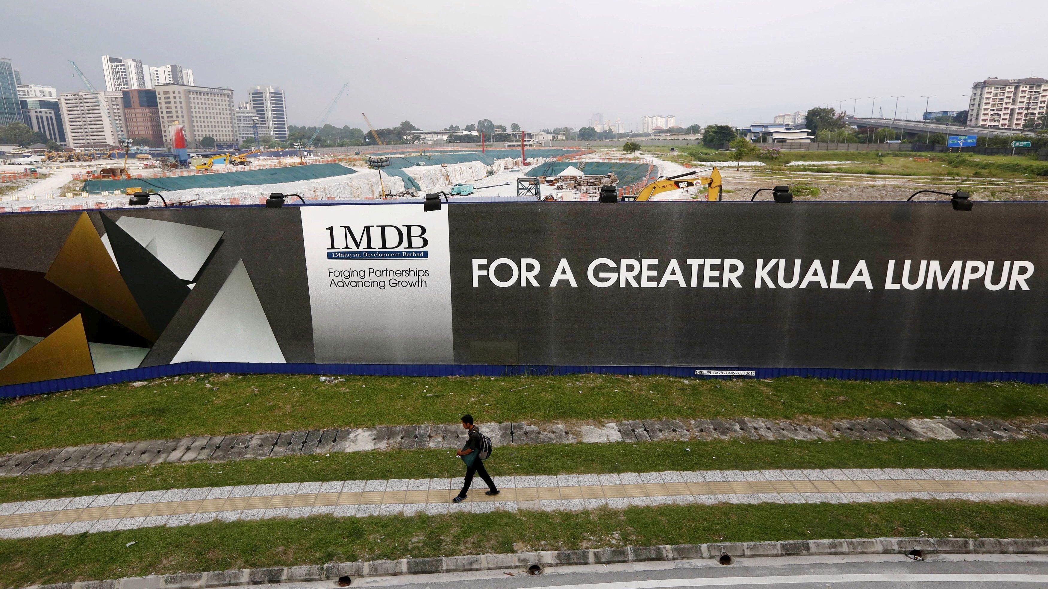 A man walks past a 1 Malaysia Development Berhad (1MDB) billboard at the funds flagship Tun Razak Exchange development in Kuala Lumpur