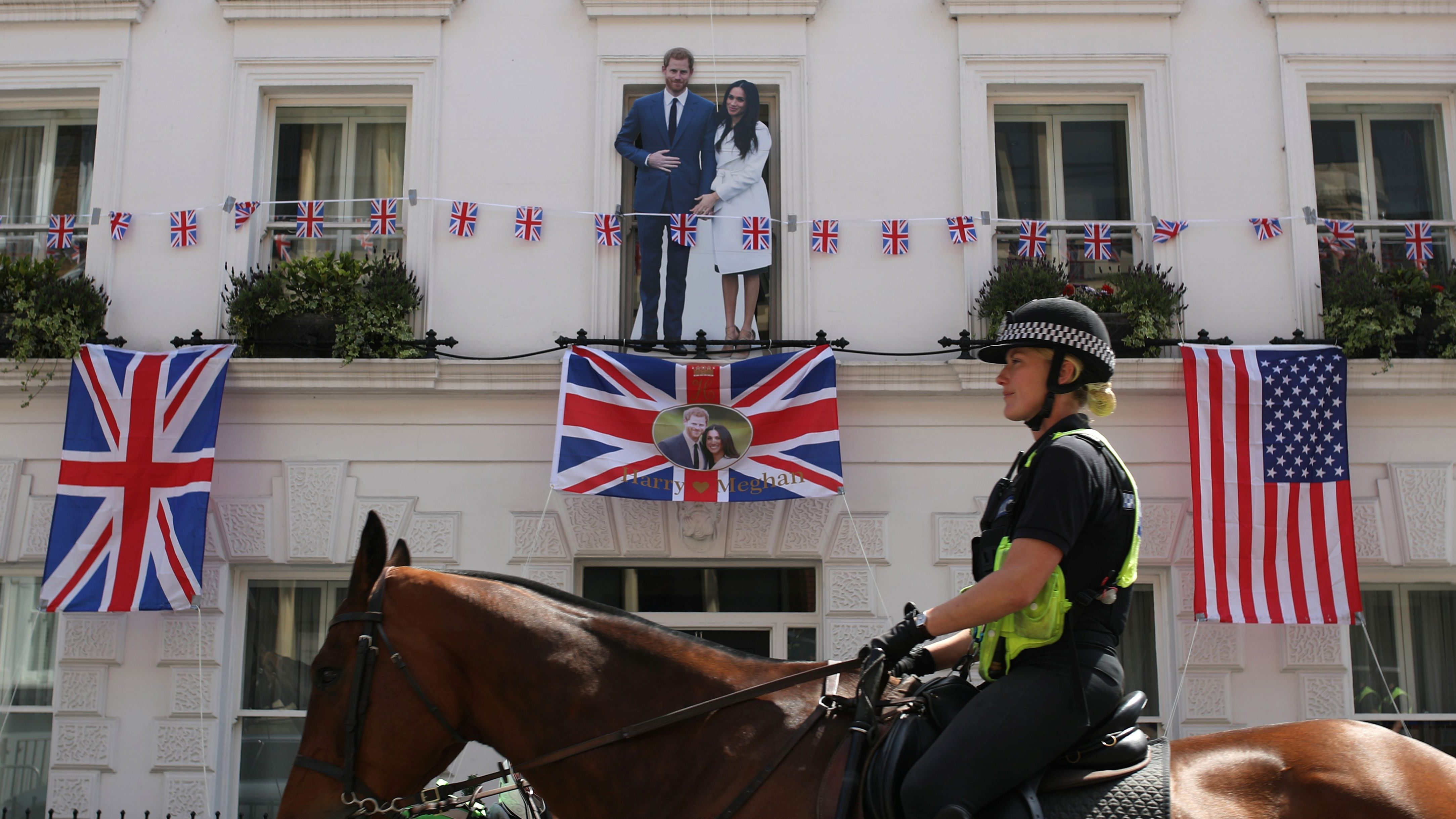 A police officer on horseback, rides past a cutout of Prince Harry and Meghan Markle, ahead of their wedding.