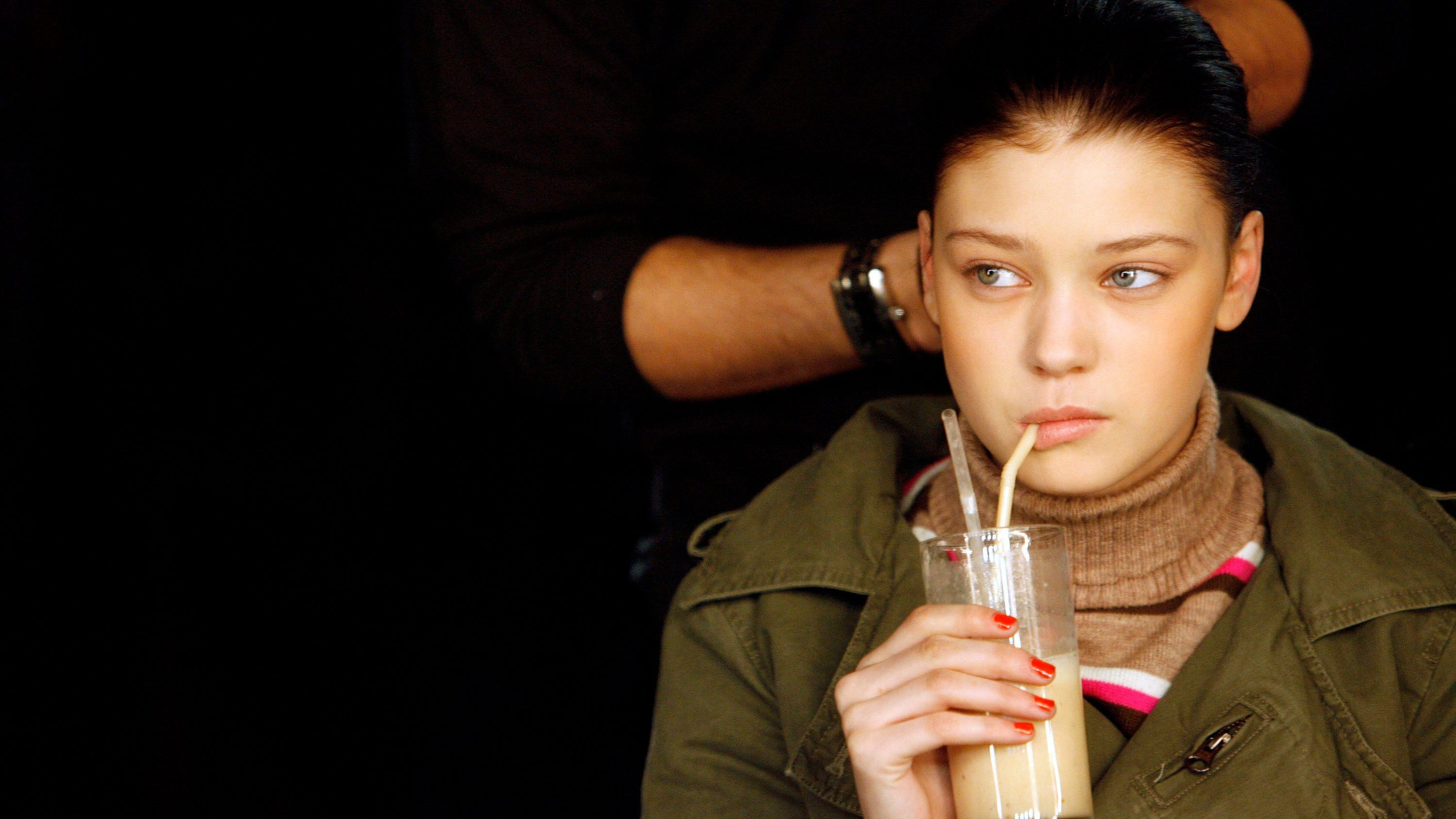 A model drinks a smoothie as she gets ready before Gharani Strok's Autumn/Winter 2007 show at London Fashion Week