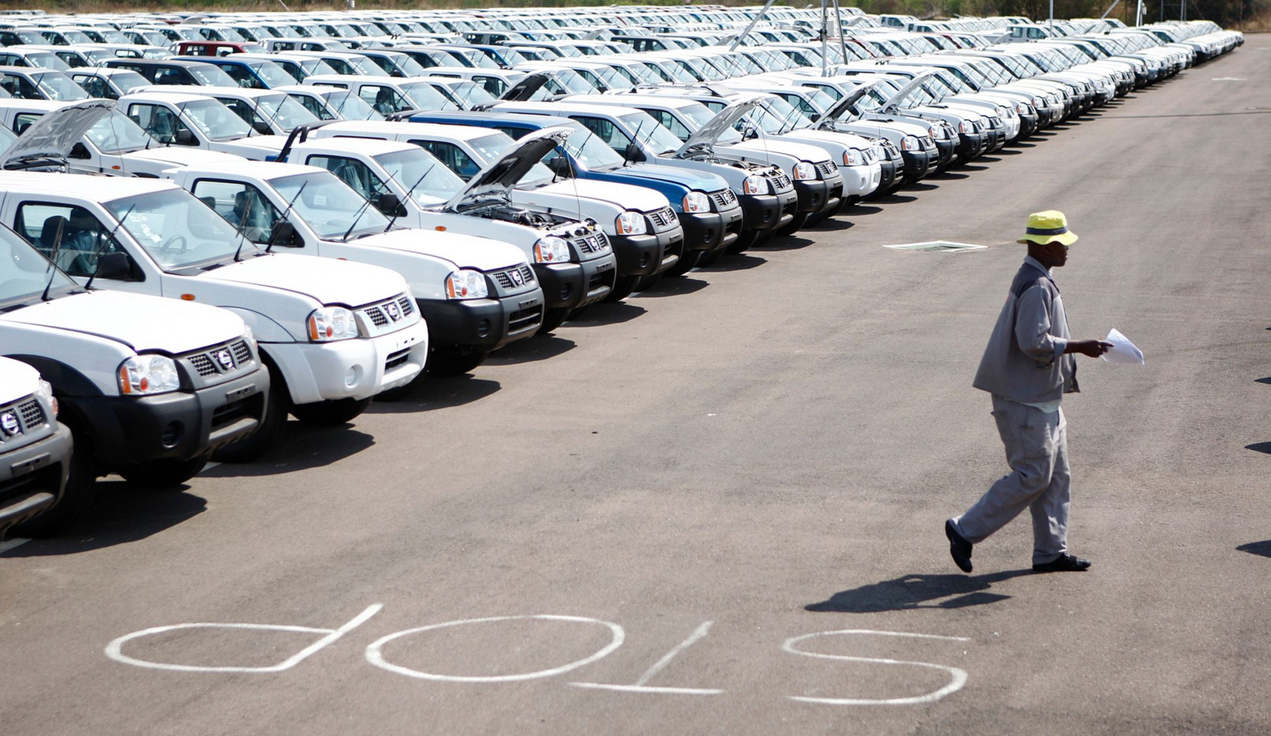 A worker walks near a row of cars at Nissan's manufacturing plant in Rosslyn