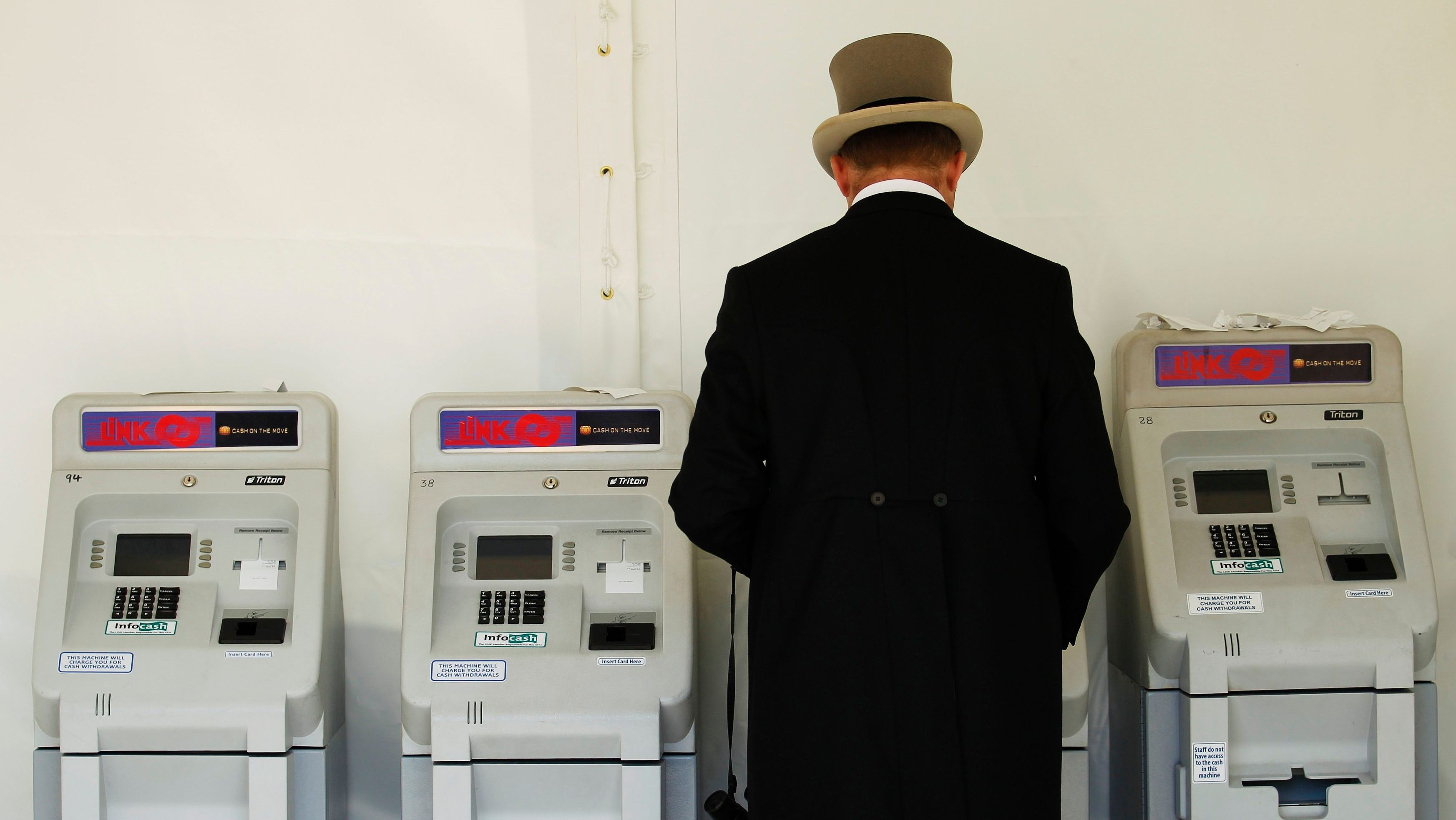 A racegoer uses a cash machine the second day of racing at Royal Ascot in southern England