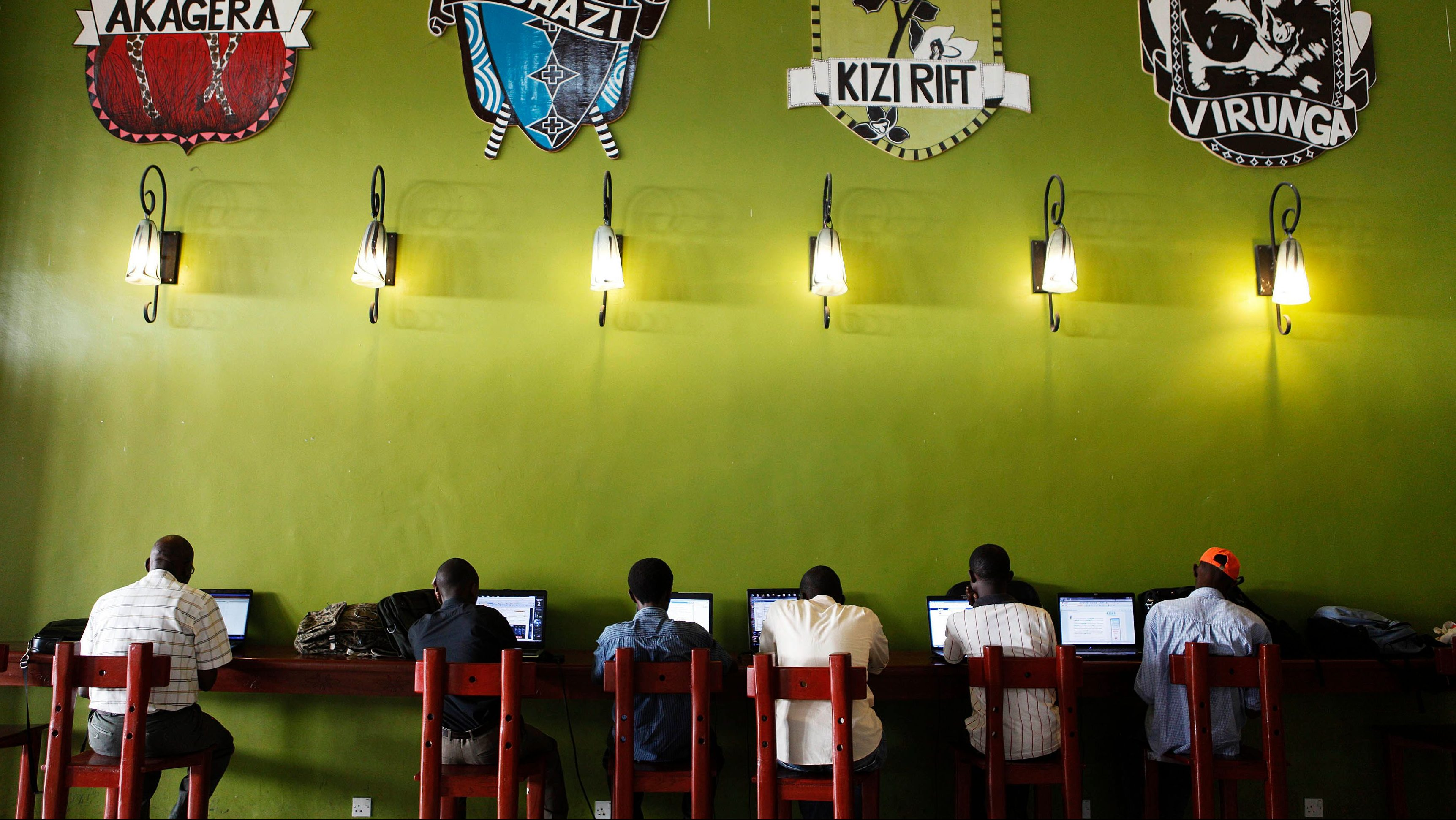 People surf the internet at a free Wi-Fi spot at Kigali international airport as results begin to trickle in from general elections, in the capital Kigali, August 9, 2010. Since Rwanda's genocide 16 years ago, incumbent President Paul Kagame has brought stability, development, foreign investment, broadband Internet and national health insurance, but critics accuse the former rebel fighter of autocratic tendencies and repression.