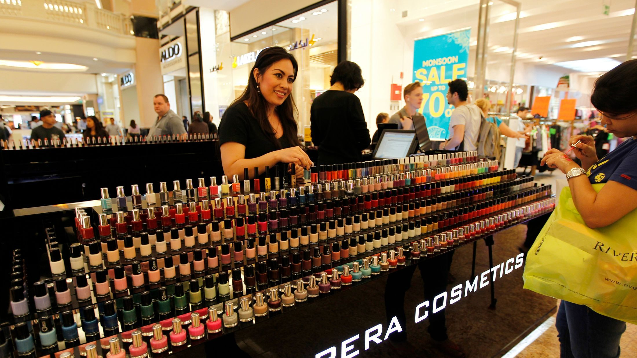 A shopper looks at bottles of nail polish displayed at a stall in the shopping centre Mall of the Emirates in Dubai, January 11, 2012. Gulf economies are continuing to grow strongly but amid a mammoth array of discounts, raffles and spending sprees at this year's Dubai Shopping Festival, there are signs consumers are becoming more value-conscious and think twice about lavishing cash after months of instability in the global economy. Picture taken January 11, 2012. To match Feature DUBAI-SHOPPING/       REUTERS/Jumana El Heloueh (UNITED ARAB EMIRATES - Tags: BUSINESS SOCIETY) - GM1E81I1SY601