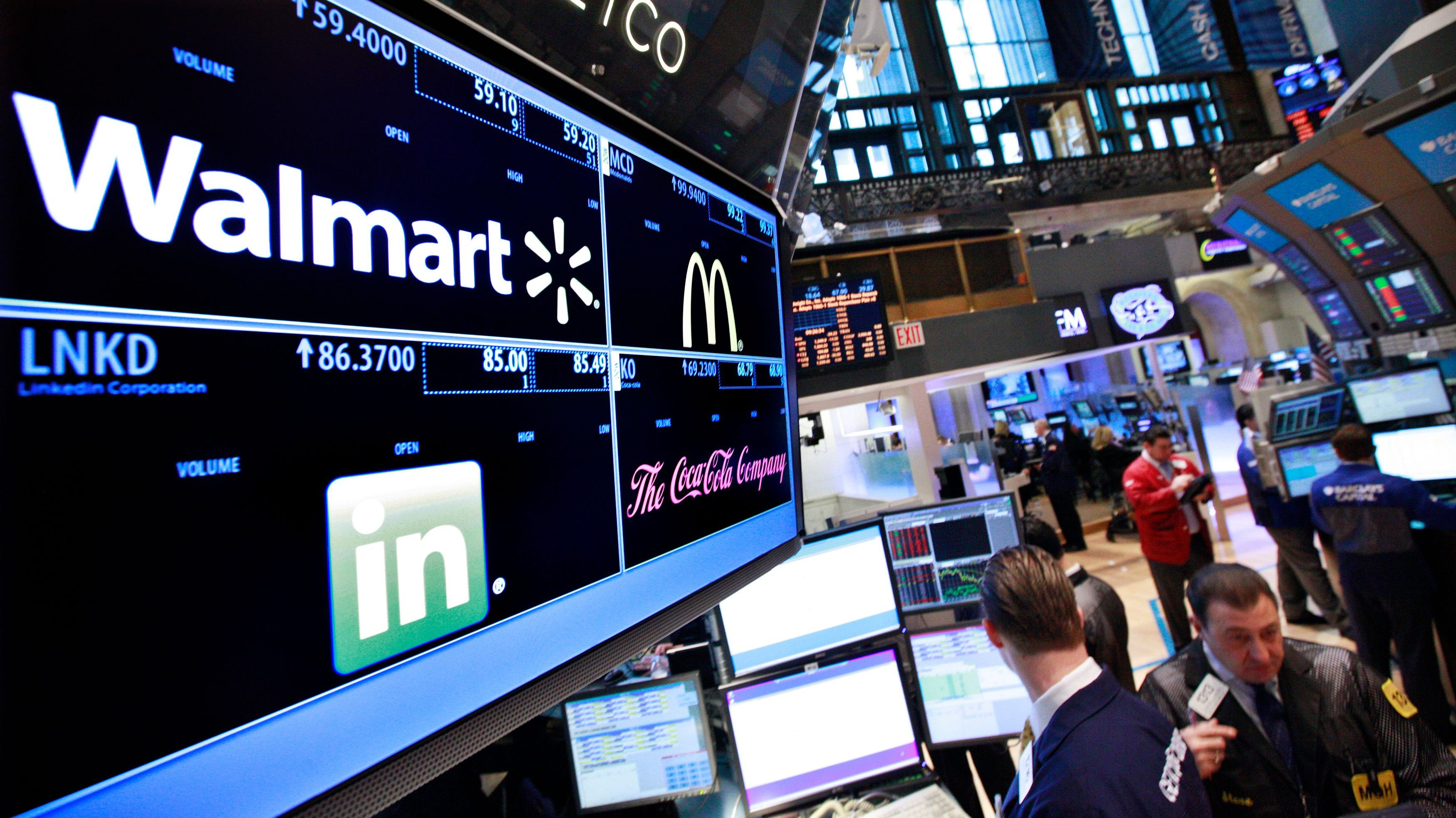 A board shows stock prices for Walmart, Linkedin, McDonald's and Coca-Cola at the booth they are traded on the floor of the New York Stock Exchange
