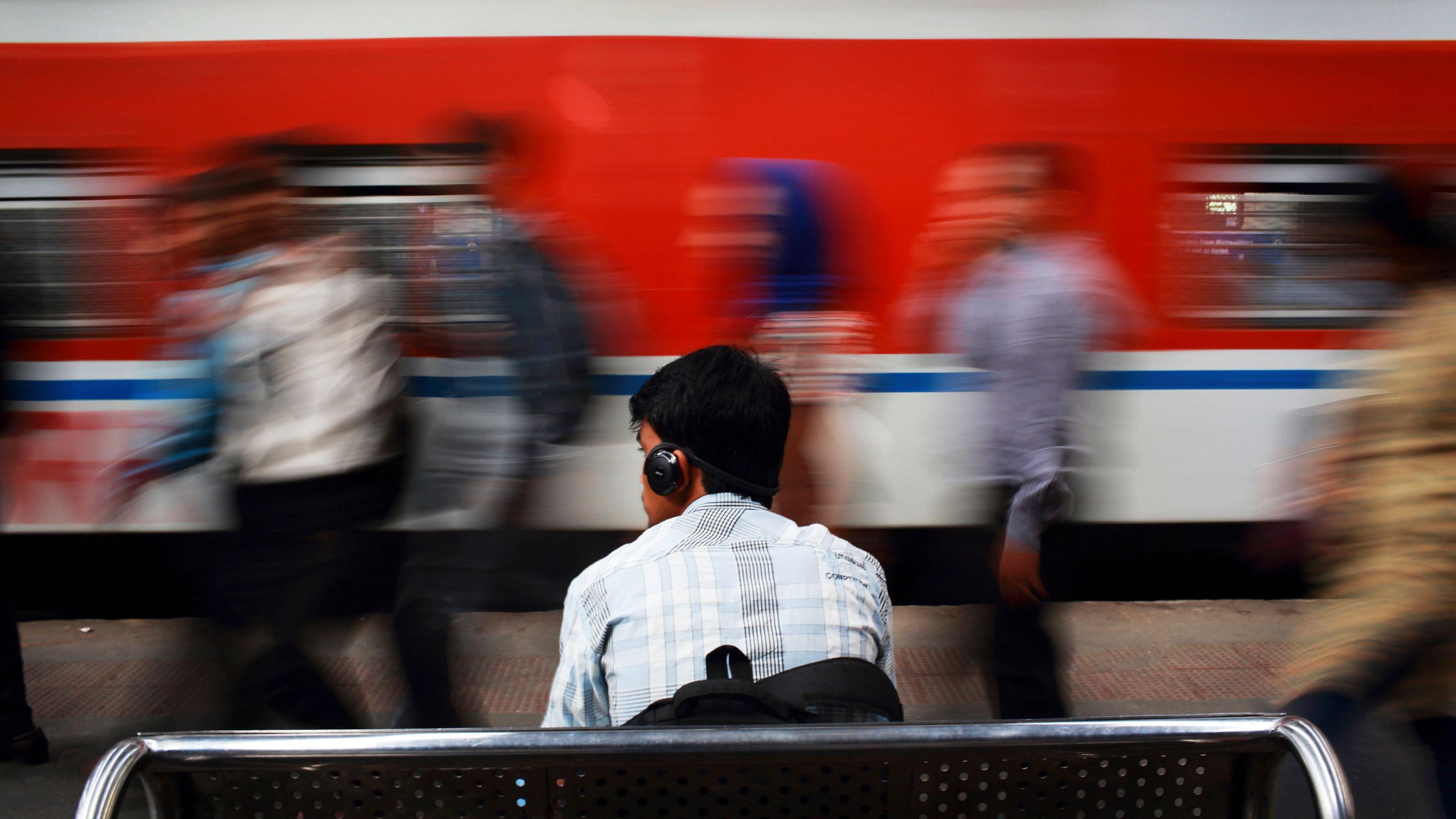 A man listens to music as he waits for his train at Churchgate railway station in Mumbai