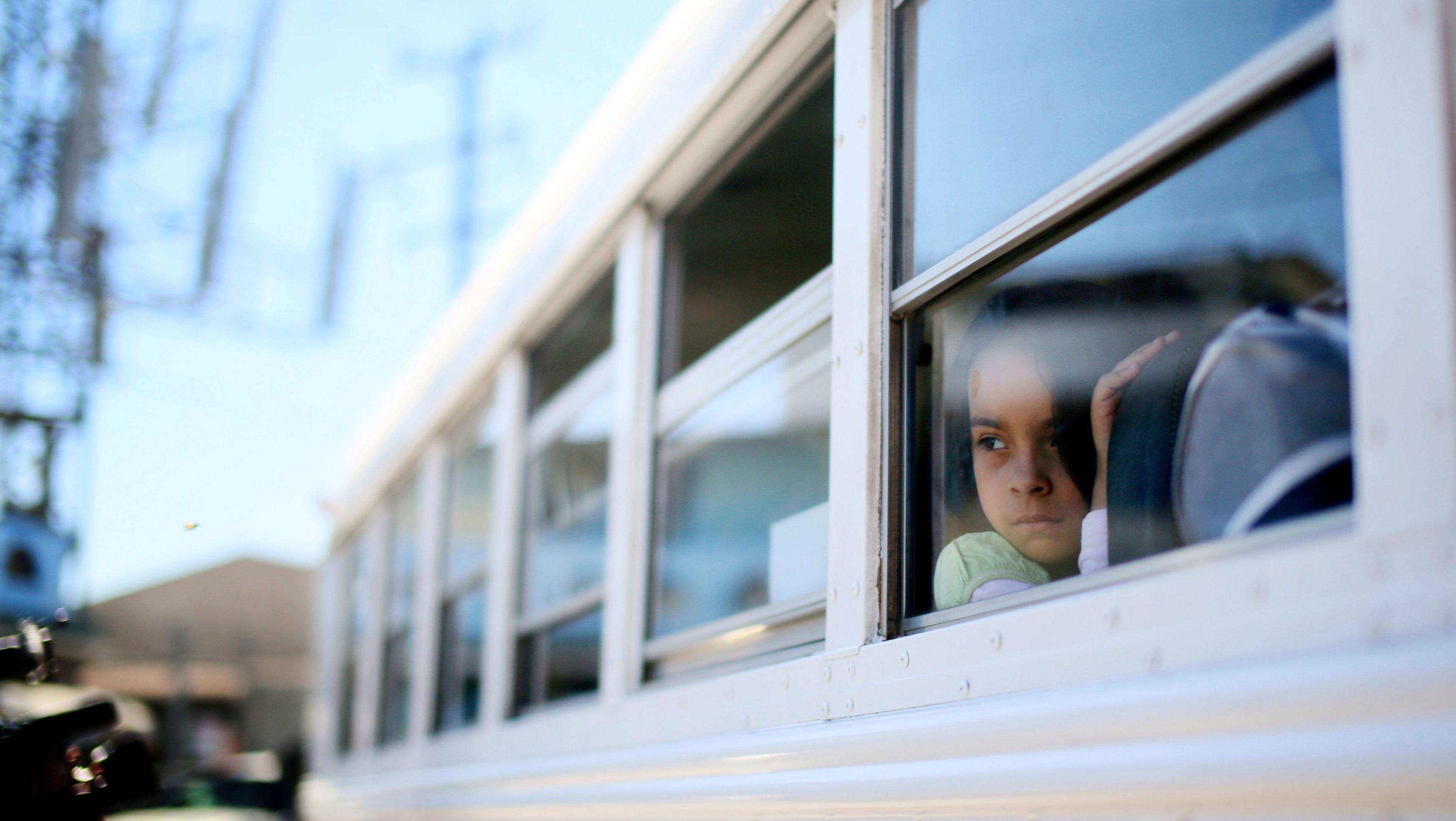 A young girl prepares to depart a bus with her parents before a protest at the U.S.-Mexico border during a Dream Act  protest in Tijuana, Mexico, March 10, 2014.  Approximately 40 protesters turned themselves in at the border in an attempt to get arrested trying to enter the United States, to bring light to deportations by the Obama administration.  REUTERS/Sandy Huffaker  (MEXICO - Tags: POLITICS SOCIETY EDUCATION CRIME LAW IMMIGRATION) - TM4EA3A1CM901