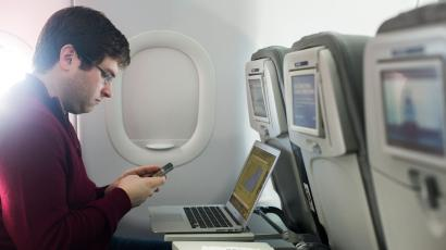 A man uses his mobile phone and laptop to test a new high speed inflight Internet service named Fli-Fi while on a special JetBlue media flight out of John F. Kennedy International Airport in New York
