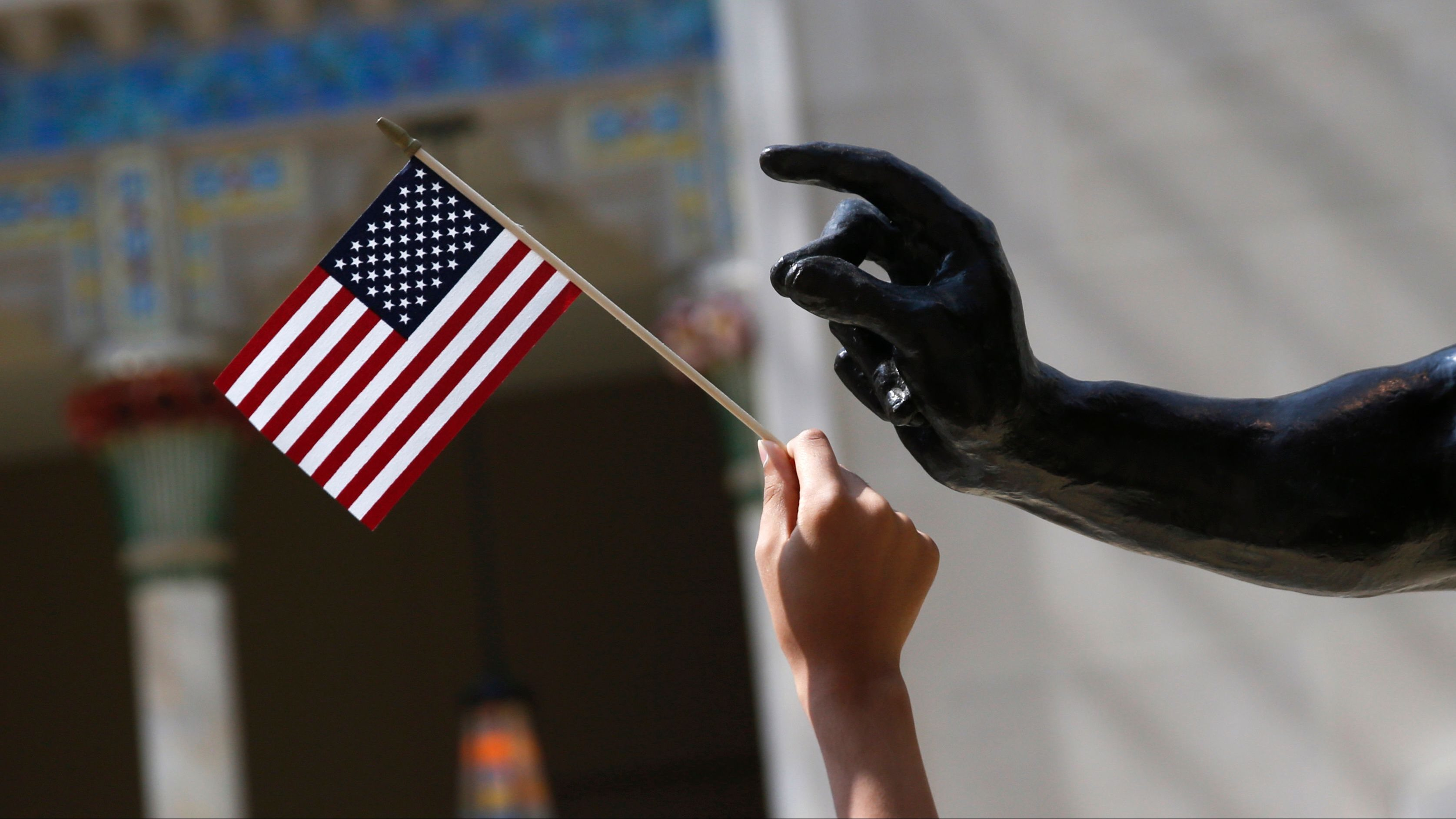 A girl holds a U.S. flag next to a sculpture after a naturalization ceremony at The Metropolitan Museum of Art in New York July 22, 2014. Seventy-five people from 42 countries became American citizens at an event held by U.S. Citizenship and Immigration Services (USCIS) at the Museum. REUTERS/Shannon Stapleton (UNITED STATES  - Tags: SOCIETY POLITICS IMMIGRATION) - GM1EA7N03K501