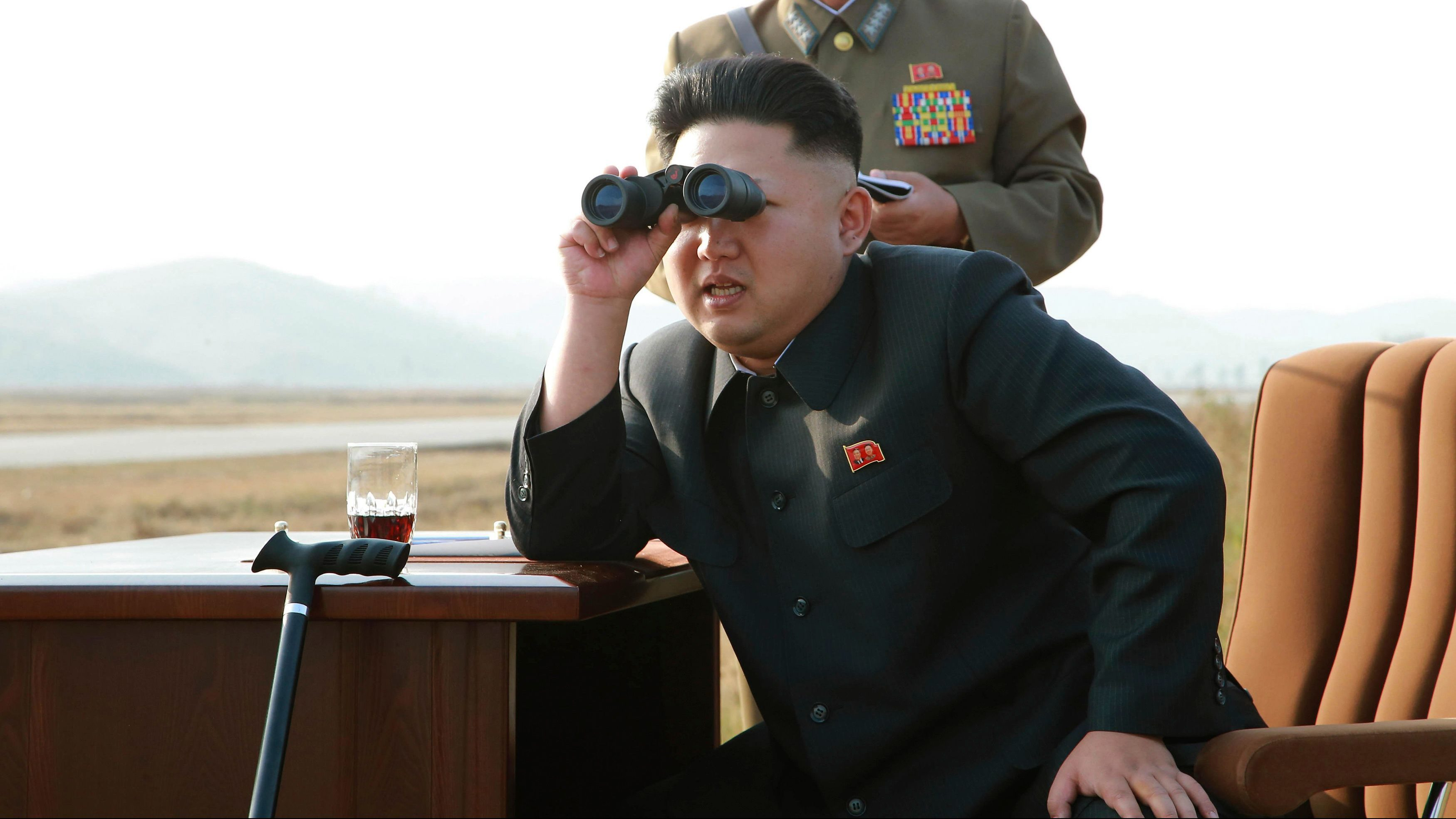 North Korean leader Kim Jong Un looks through a pair of binoculars as he guides a flight drill for the inspection of airmen of the Korean People's Army (KPA) Air and Anti-Air Force in this undated photo released by North Korea's Korean Central News Agency (KCNA) in Pyongyang October 30, 2014.