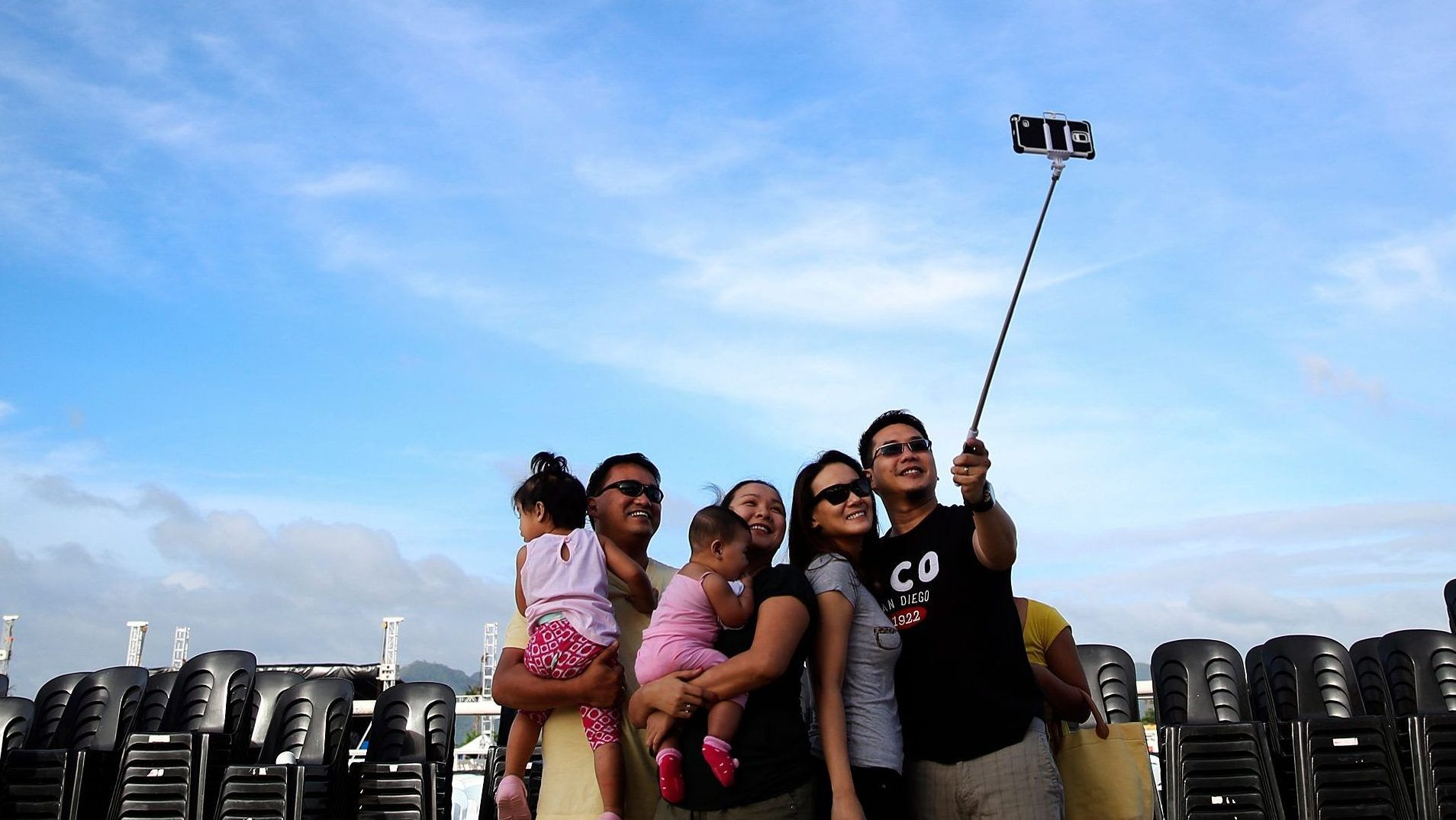 """People take picture of themselves using a """"selfie stick"""" near the altar from which Pope Francis will hold a mass at Tacloban's airport, January 16, 2015. On his first visit to Asia's largest Catholic nation, the pontiff will visit the central province of Leyte, which is still struggling to recover from Typhoon Haiyan that killed 6,300 people in 2013. About two million people are expected to attend an open-air mass on Saturday at Tacloban City airport, almost completely destroyed by Haiyan. REUTERS/Damir Sagolj (PHILIPPINES - Tags: RELIGION SOCIETY) - GM1EB1G10VH01"""