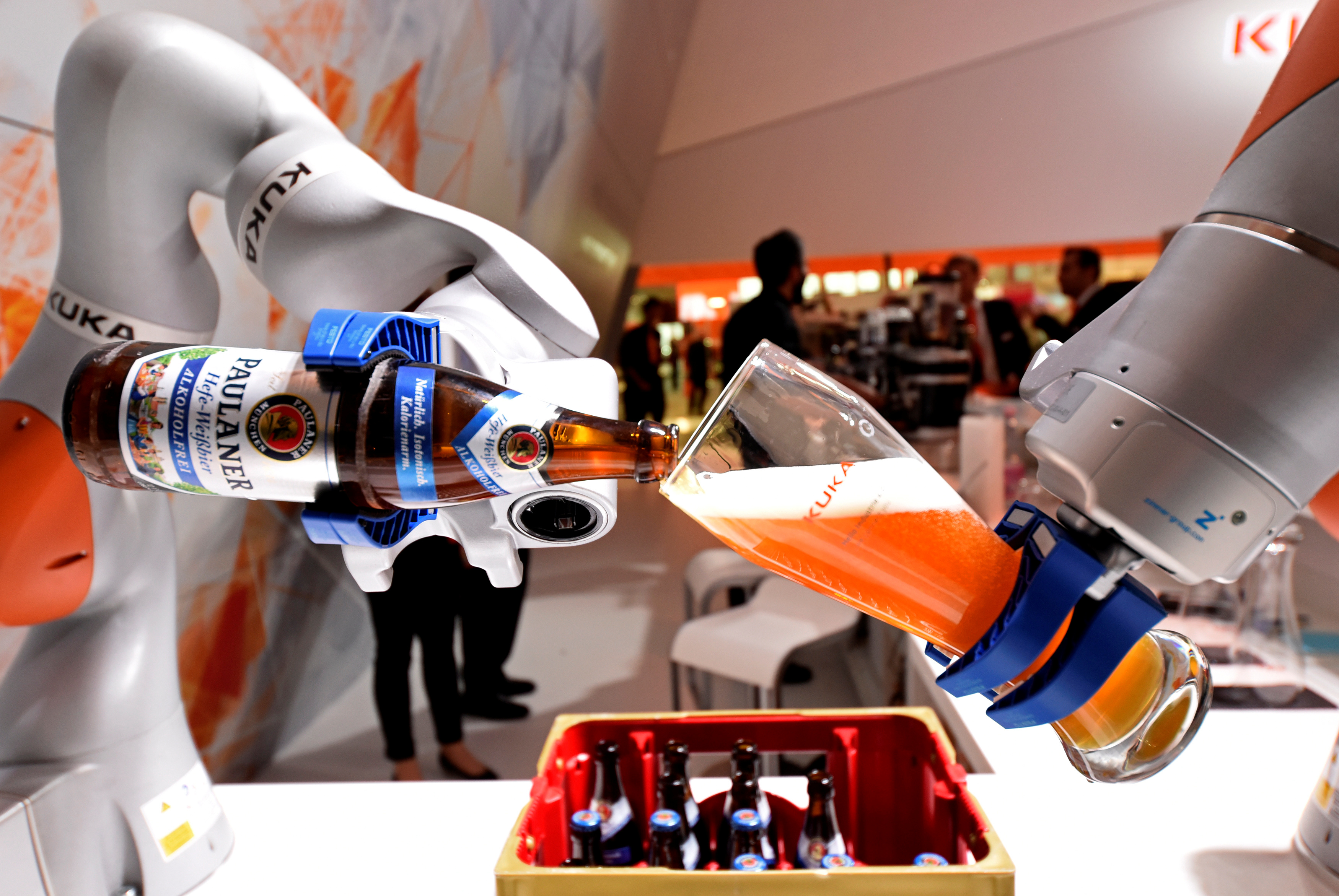 """A robotic arm fills a glass with Bavarian Weiss beer at the booth of German company Kuka at the world's biggest industrial fair, """"Hannover Fair"""", in Hanover, Germany April 24, 2017. REUTERS/Fabian Bimmer - RC1C5CEE06B0"""