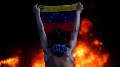 A protester holds a national flag as a bank branch, housed in the magistracy of the Supreme Court of Justice, burns during a rally against Venezuela's President Nicolas Maduro, in Caracas