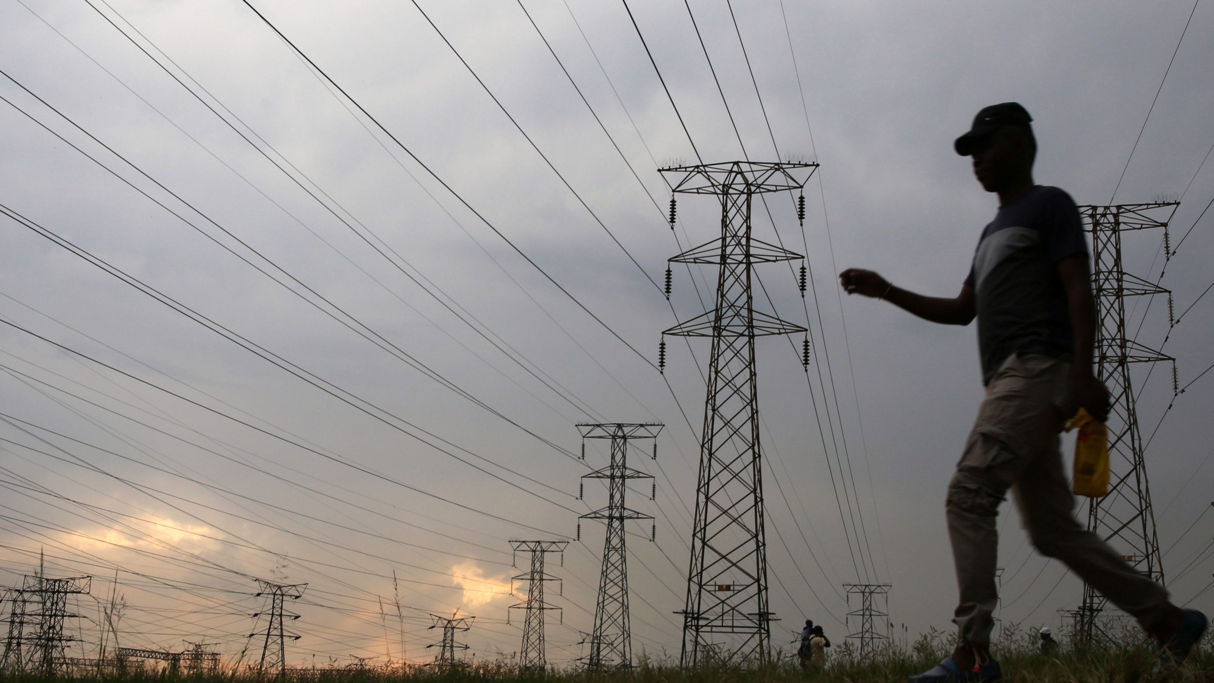 A man walks past electricity pylons in Soweto, South Africa.