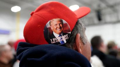 A supporter wears a hat with a Trump button at a Trump rally