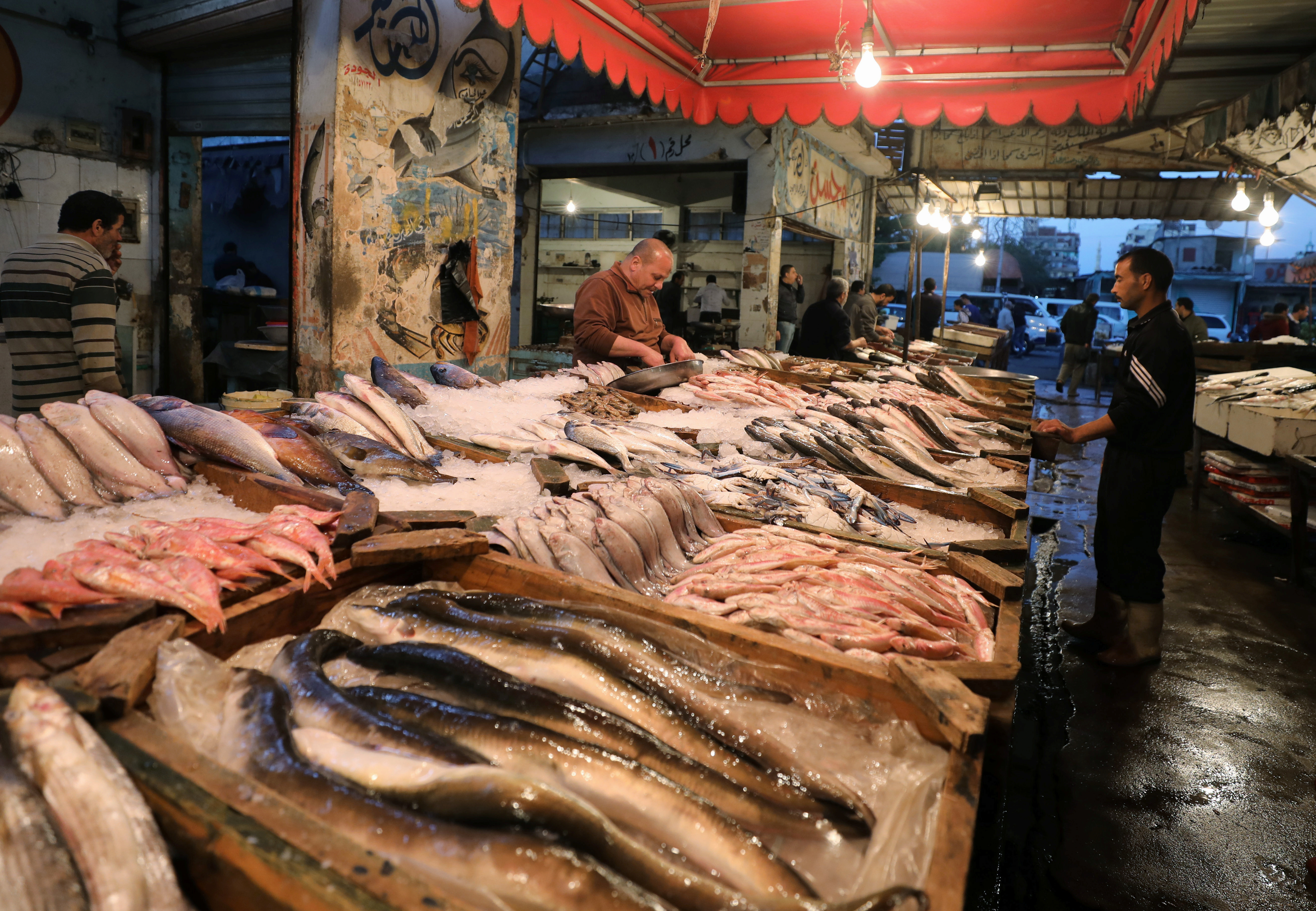 Vendors wait for customers in a fish market near the canal of Port Said