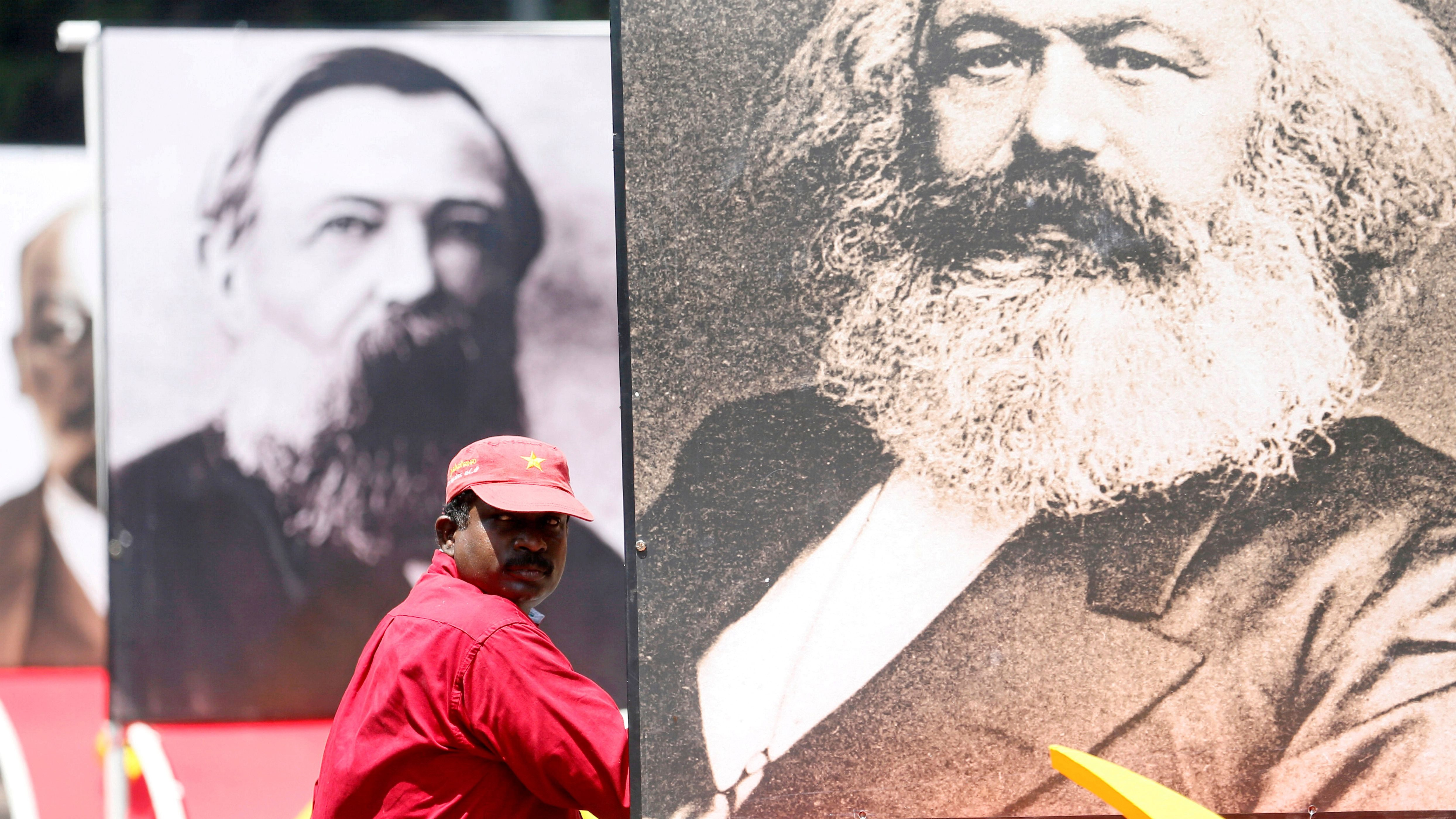 A man looks on next to an image of Karl Marx during a May Day rally organized by Front Line Socialist Party in Colombo, Sri Lanka May 1,2018.