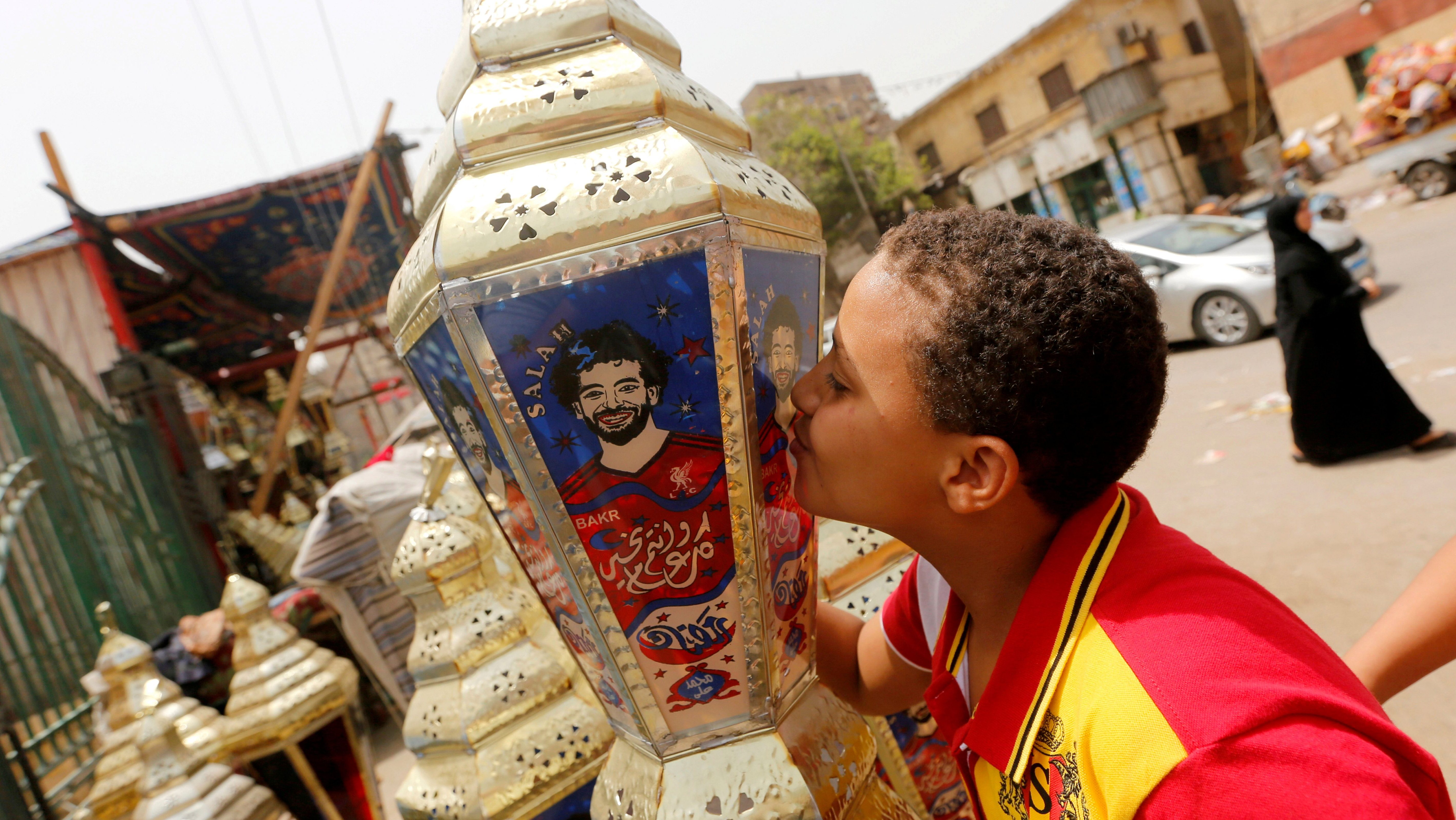 "An Egyptian boy kisses the traditional decorative lanterns known as ""Fanous"" bearing the image of Liverpool's Egyptian forward soccer player Mohamed Salah, at a market, before the beginning of the holy fasting month of Ramadan in Cairo, Egypt May 2, 2018. Arabic words read ""Ramadan is sweeter with Salah""."