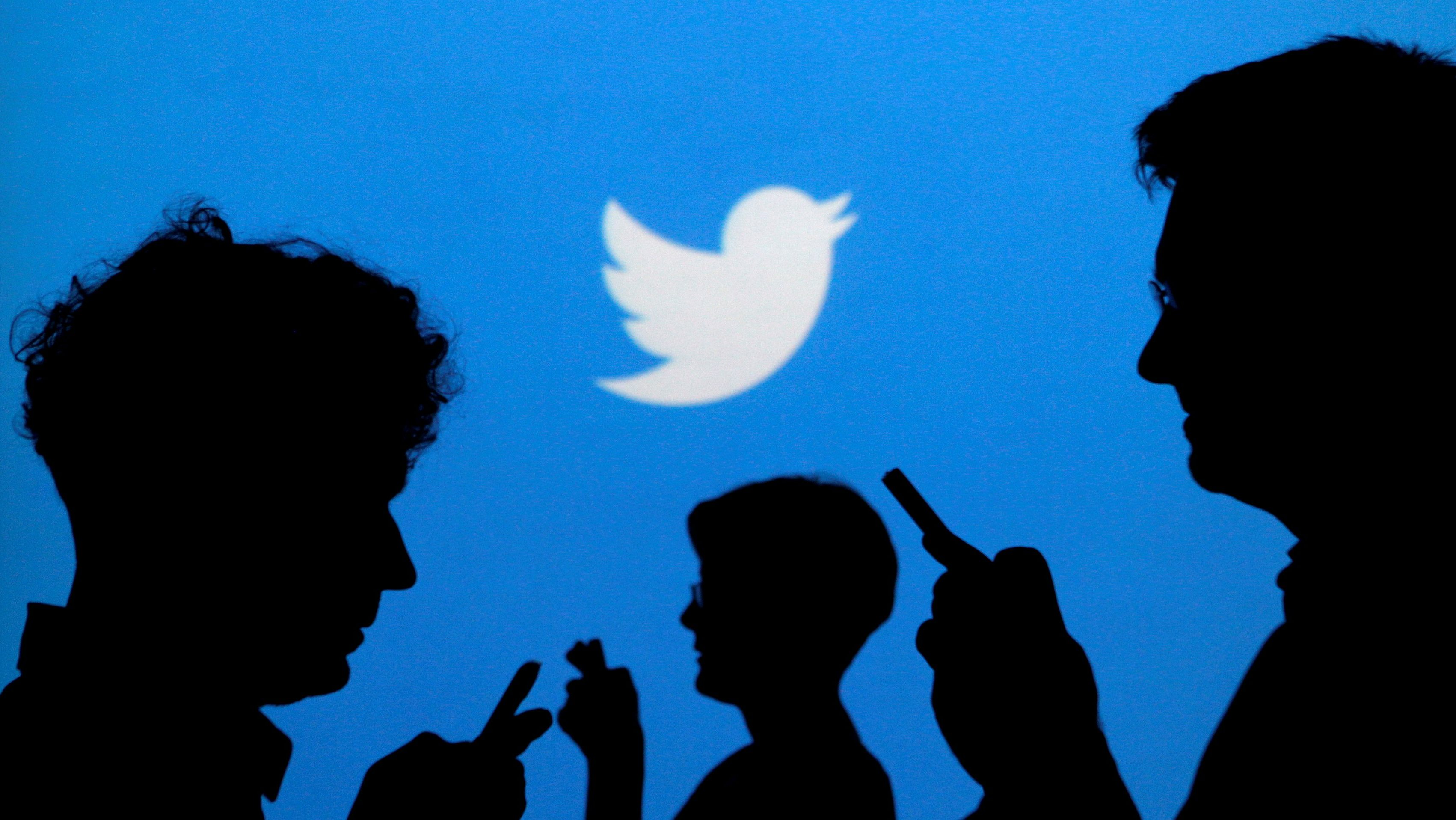 FILE PHOTO:    People holding mobile phones are silhouetted against a backdrop projected with the Twitter logo in this illustration picture taken in  Warsaw September 27, 2013.