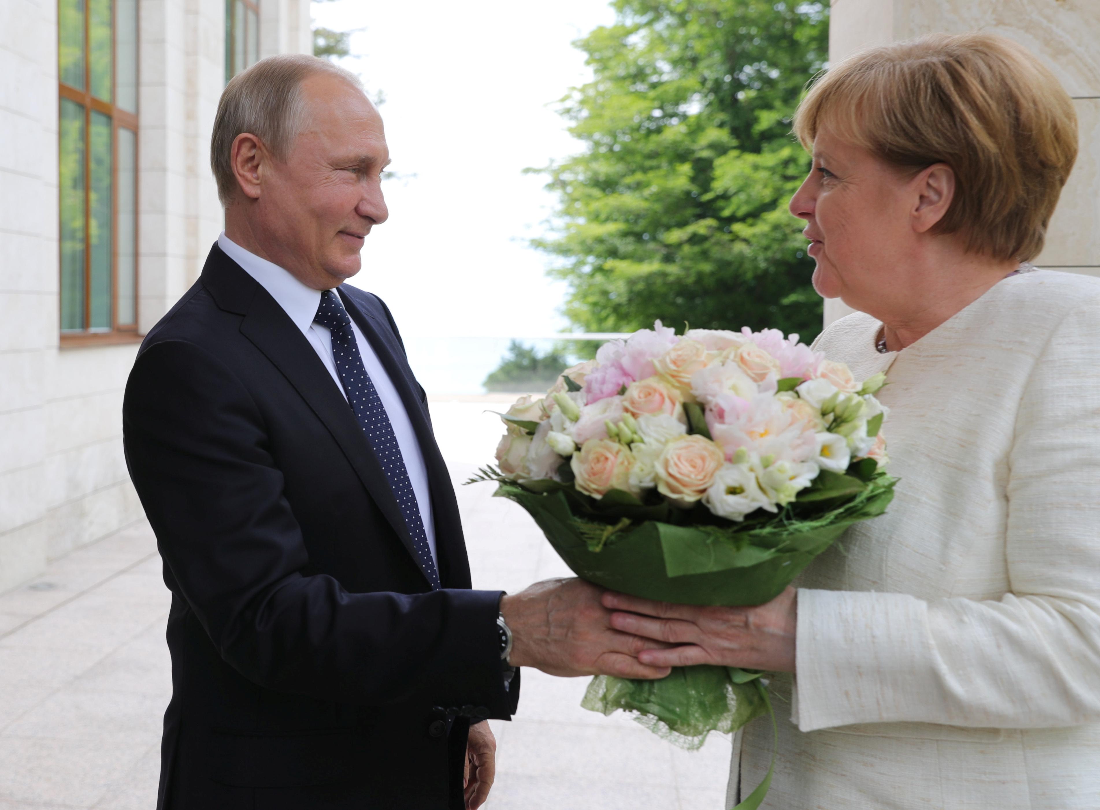 Russian President Vladimir Putin welcomes German Chancellor Angela Merkel during their meeting in the Black Sea resort of Sochi, Russia May 18, 2018. Sputnik/Mikhail Klimentyev/Kremlin via REUTERS ATTENTION
