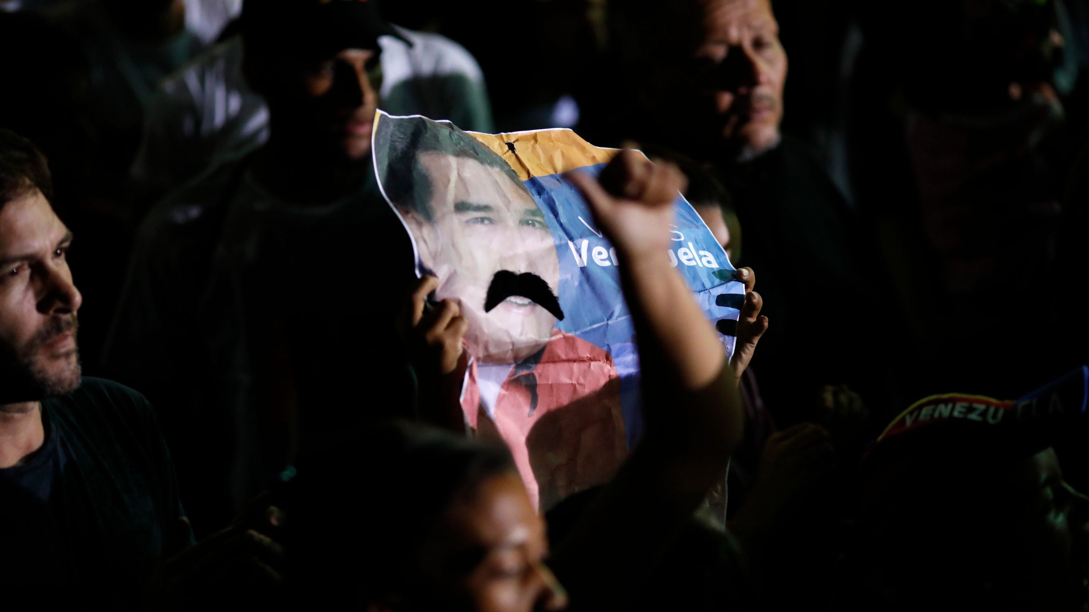 An image depicting Venezuela's President Nicolas Maduro's mustache is held up while he speaks after the results of the election were released