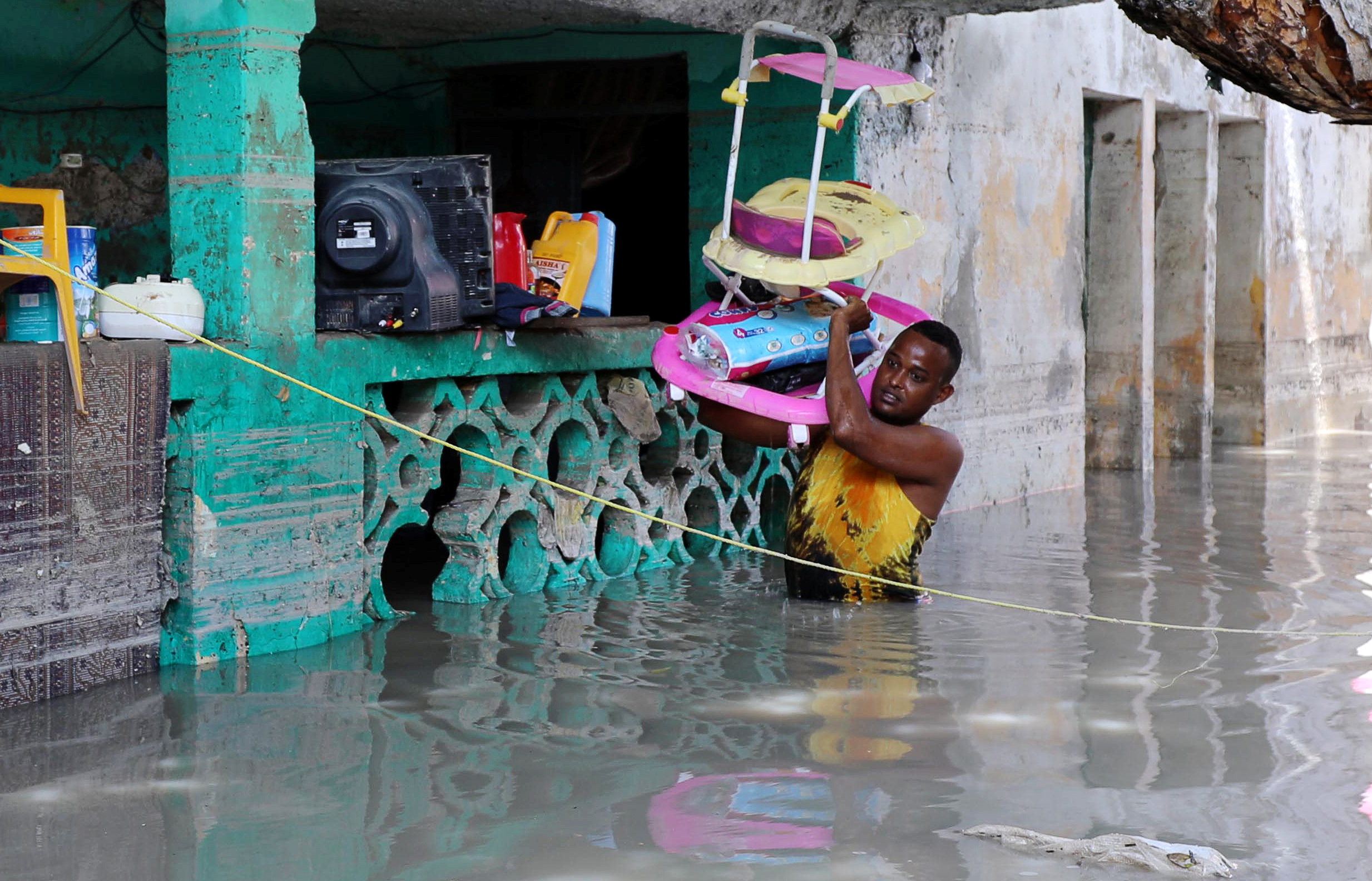 A resident evacuates furniture after rain water flooded his home in Mogadishu, Somalia May 21, 2018.