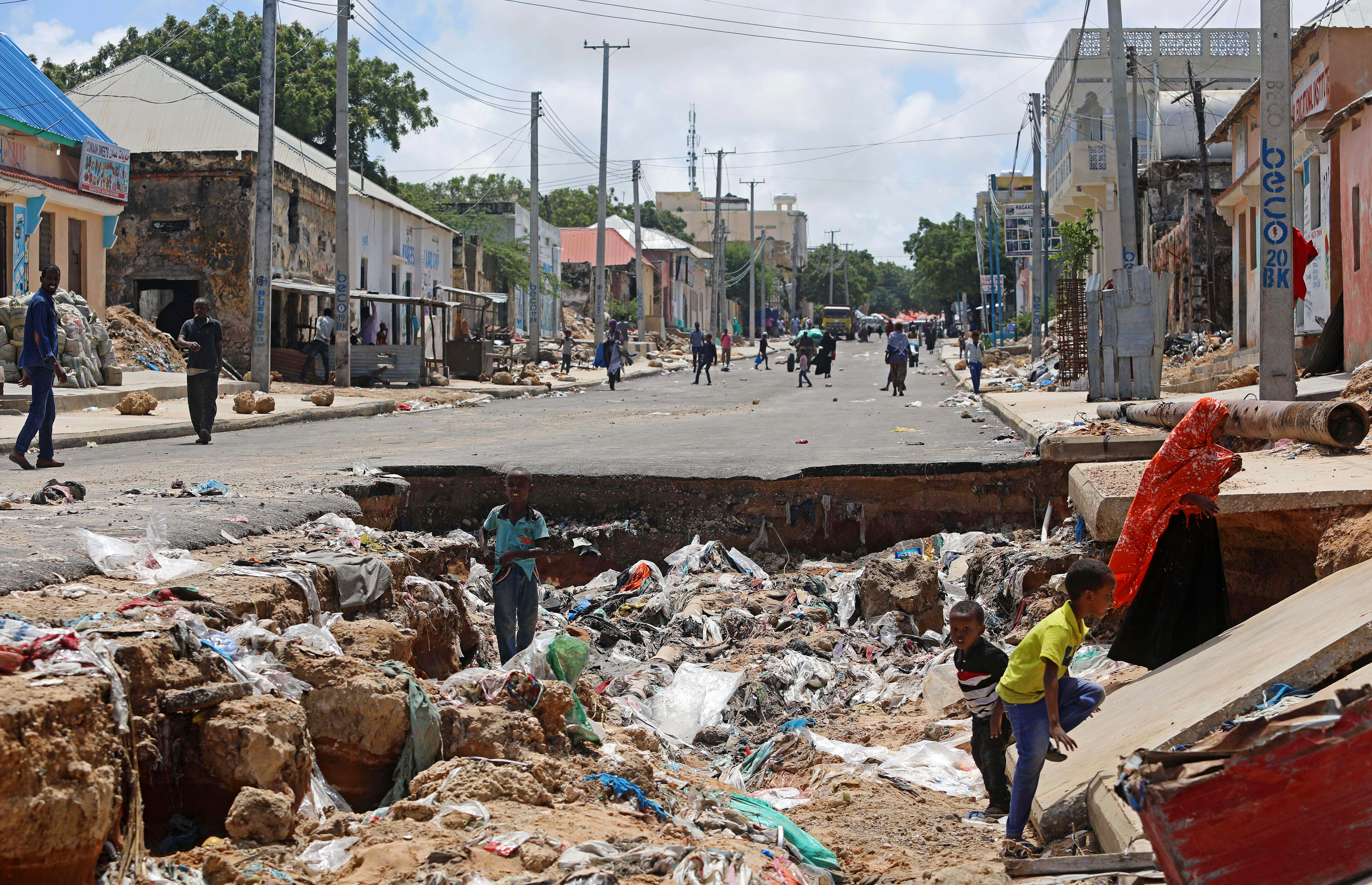 Children play near a road destroyed by rain water that flooded their street in Mogadishu, Somalia May 21, 2018.