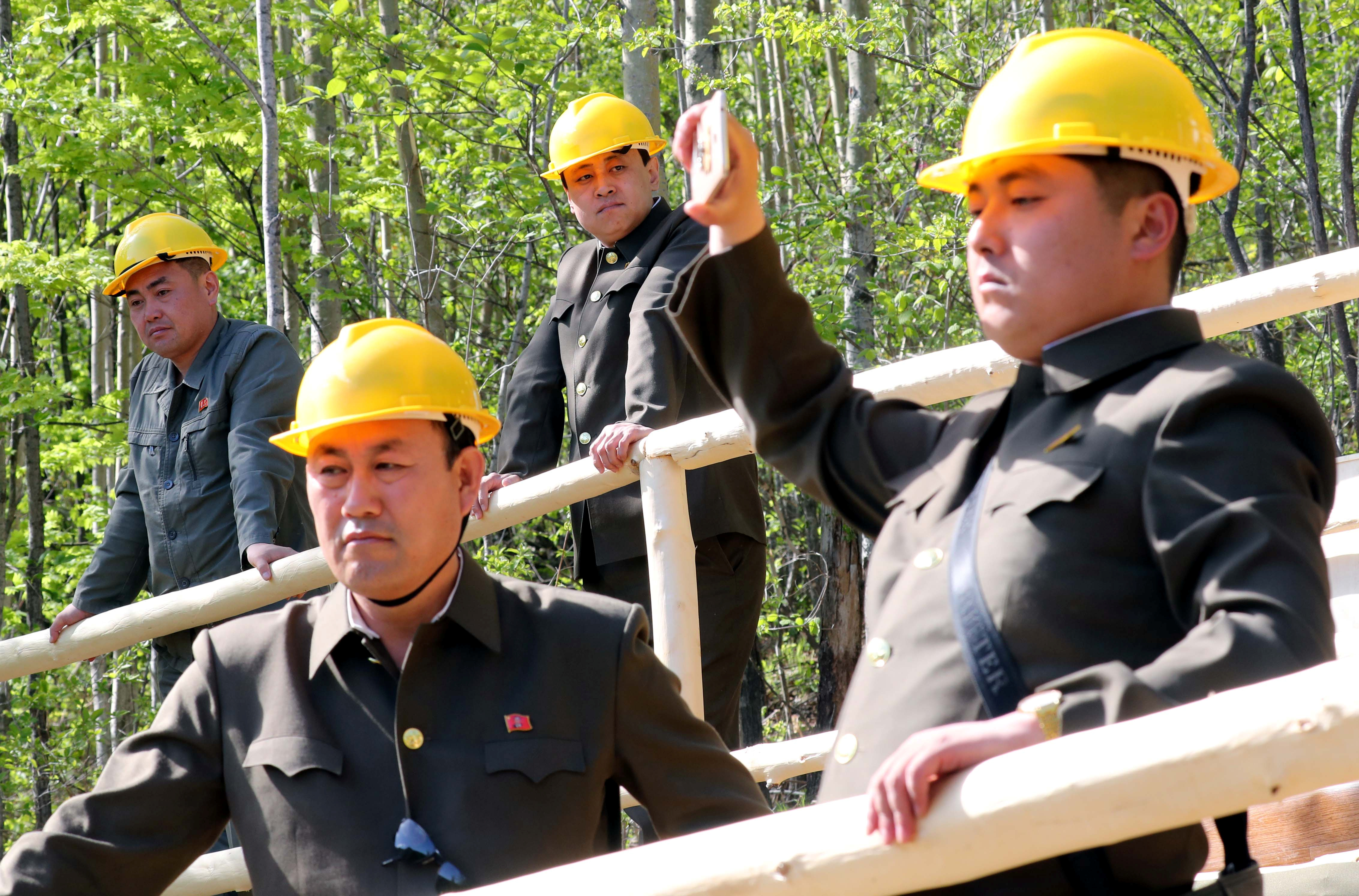 North Korean officials watch the dismantlement process of Punggye-ri nuclear test ground in Punggye-ri, North Hamgyong Province, North Korea May 24, 2018. Picture taken May 24, 2018.