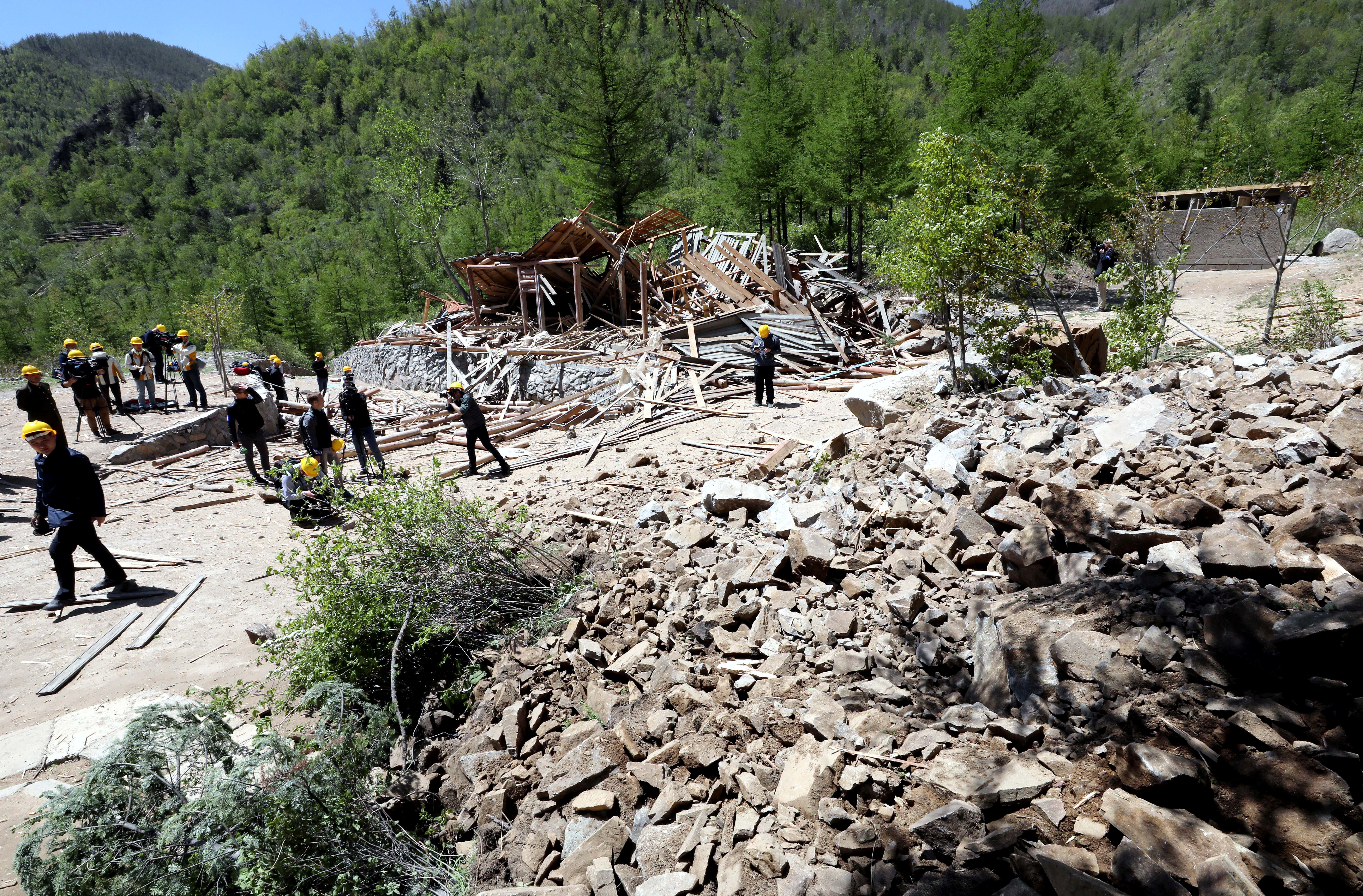 Journalists and North Korean officials look around the site where the 2nd tunnel and an observatory of Punggye-ri nuclear test ground were blown up during the dismantlement process in Punggye-ri, North Hamgyong Province, North Korea May 24, 2018.