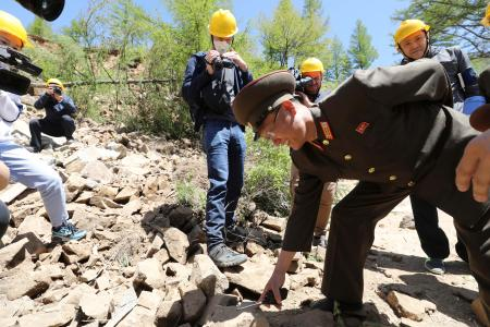 A North Korean official points a file of stones as he explains to journalists after the second tunnel of Punggye-ri nuclear test ground was blown up during the dismantlement process in Punggye-ri, North Hamgyong Province, North Korea May 24, 2018. Picture taken May 24, 2018.