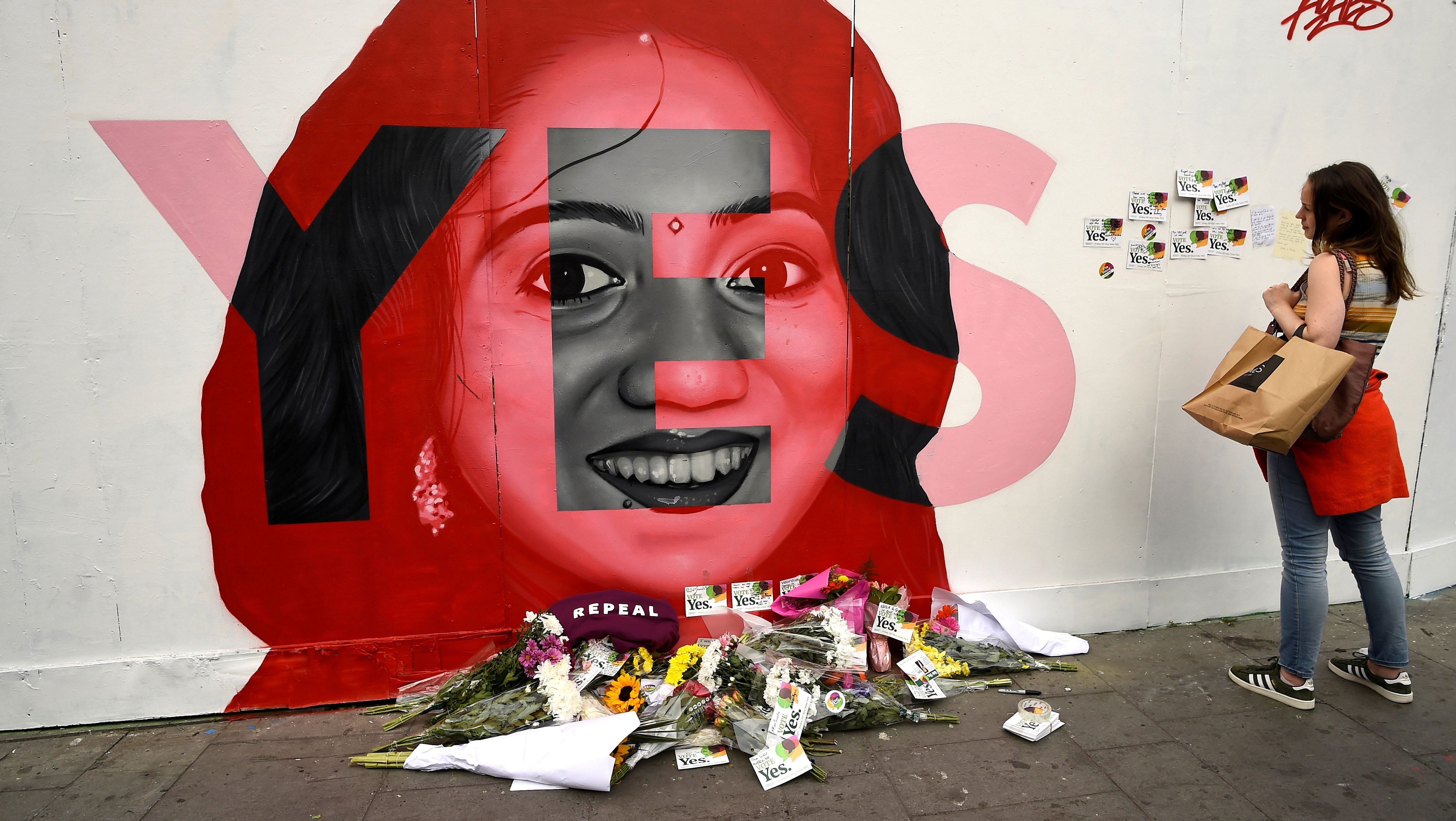 A woman looks at a new mural of Savita Halappanavar with flowers placed beneath it put up on the day of the Abortion Referendum on liberalising abortion laws in Dublin, Ireland May 25, 2018.