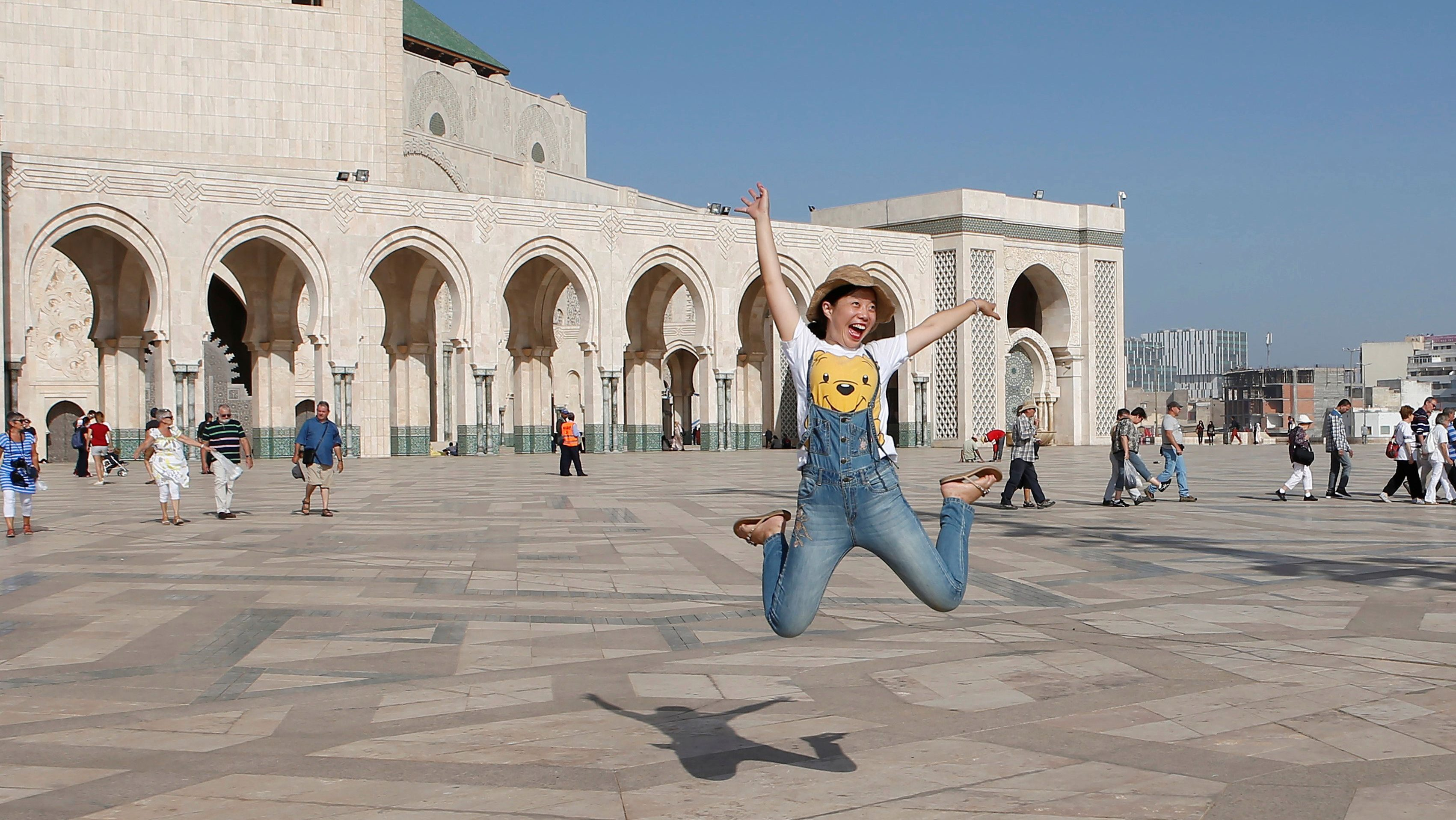 Chinese tourists jump as they pose for photographs at the esplanade of the Hassan II Mosque in Casablanca, October 6, 2016.