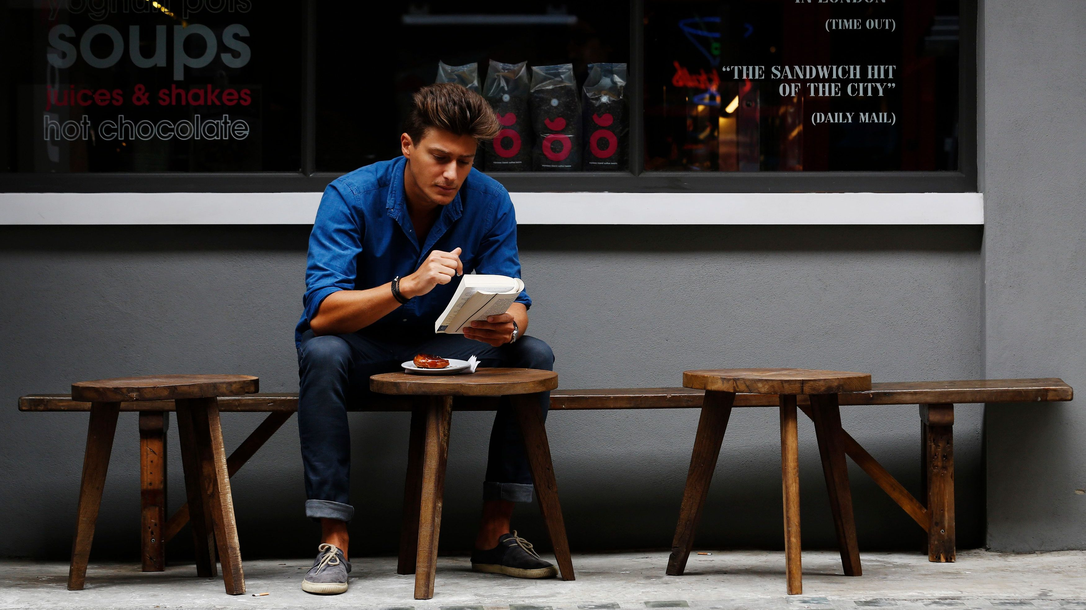 A man reads a book outside a cafe in central London