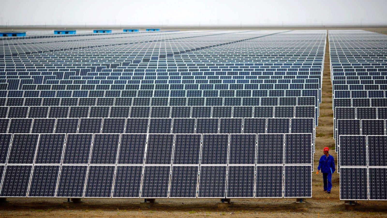 A worker inspects solar panels at a solar farm in Dunhuang, 950km (590 miles) northwest of Lanzhou, Gansu Province September 16, 2013. China is pumping investment into wind power, which is more cost-competitive than solar energy and partly able to compete with coal and gas. China is the world's biggest producer of CO2 emissions, but is also the world's leading generator of renewable electricity. Environmental issues will be under the spotlight during a working group of the Intergovernmental Panel on Climate Change, which will meet in Stockholm from September 23-26. Picture taken September 16, 2013. REUTERS/Carlos Barria (CHINA - Tags: ENERGY BUSINESS ENVIRONMENT TPX IMAGES OF THE DAY) - GM1E99M14O801