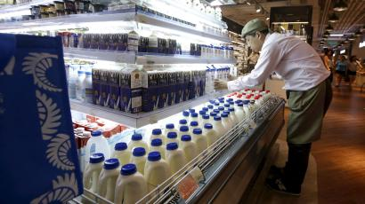 A salesman arranges milk products imported from Australia at a supermarket inside IAPM mall in Shanghai