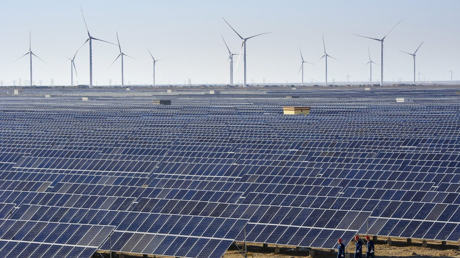 Workers walk past solar panels and wind turbines (rear) at a newly-built power plant in Hami, Xinjiang Uighur Autonomous Region, China, September 17, 2015. China's power consumption in August rose 1.9 percent from a year earlier to 512.4 billion kilowatt-hours (kWh), figures from the country's National Energy Administration (NEA) showed on Tuesday. Picture taken September 17, 2015. REUTERS/Stringer CHINA OUT. NO COMMERCIAL OR EDITORIAL SALES IN CHINA  - GF10000218074