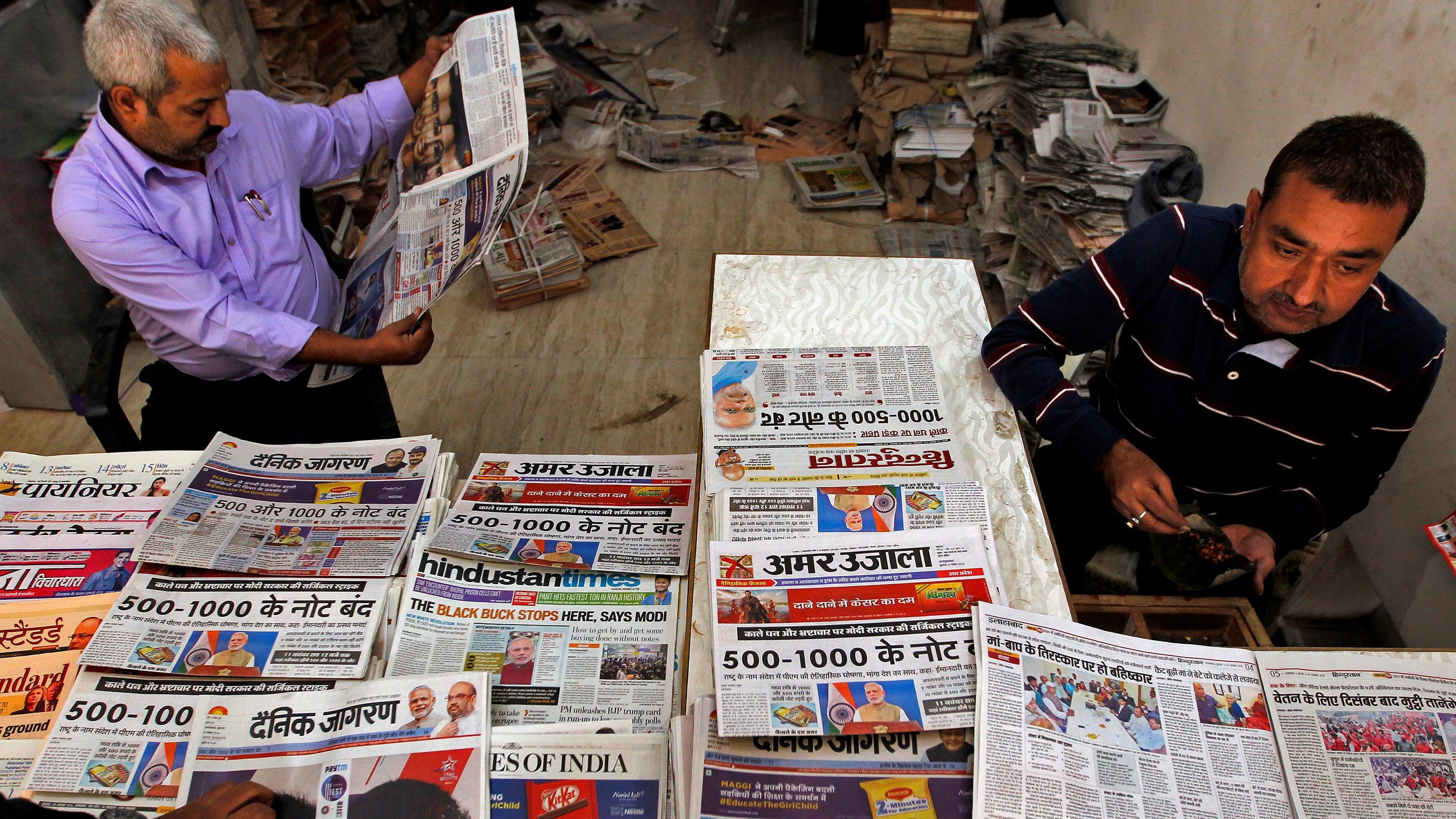 A man reads a cover story in a daily national newspaper about the withdrawal of 500 and 1000 rupee banknotes from circulation across India, at a roadside stall in Allahabad