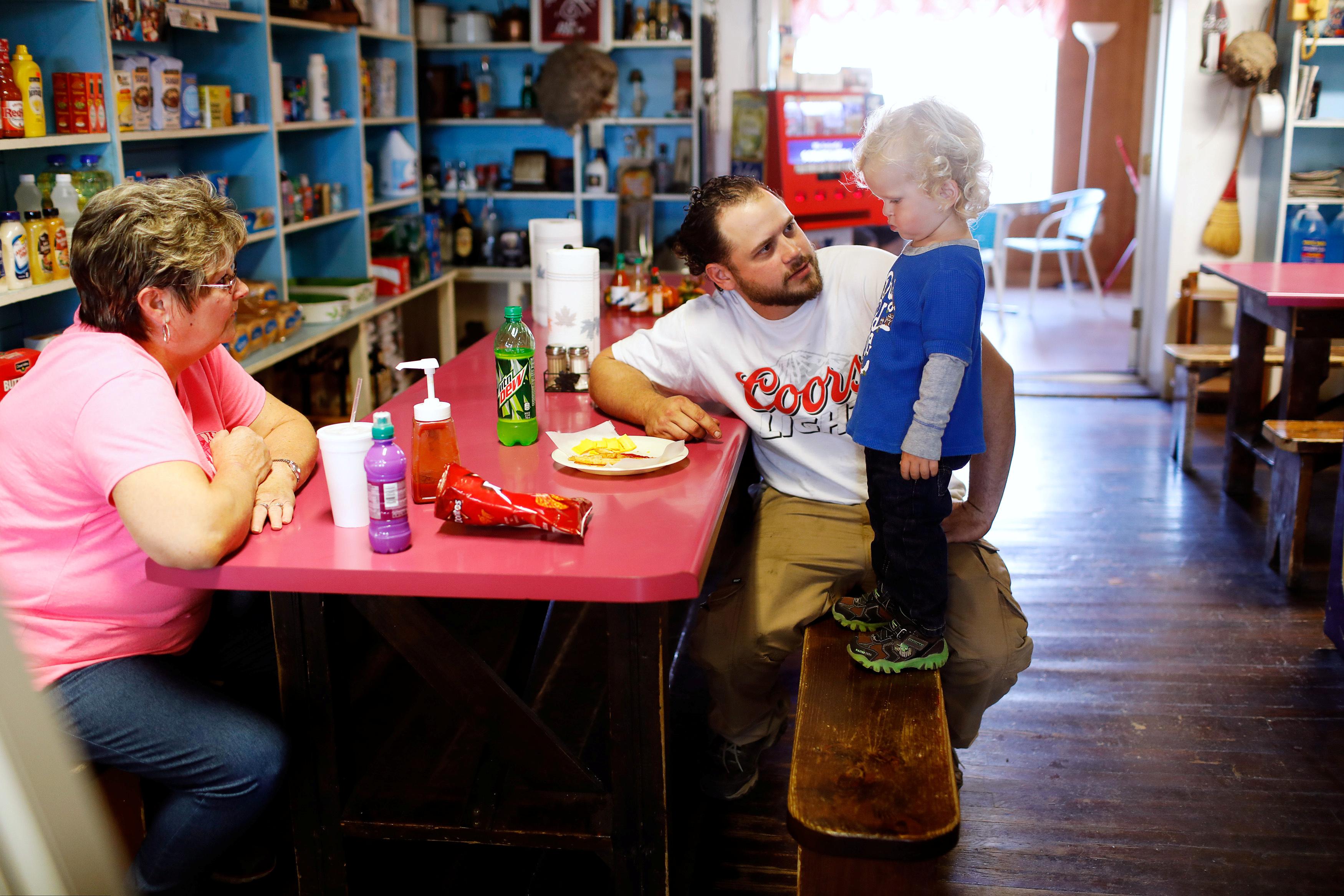 Employee Joyce Chandler looks on as Antonin Bohac encourages his son, Sawyer, to eat in Bixby