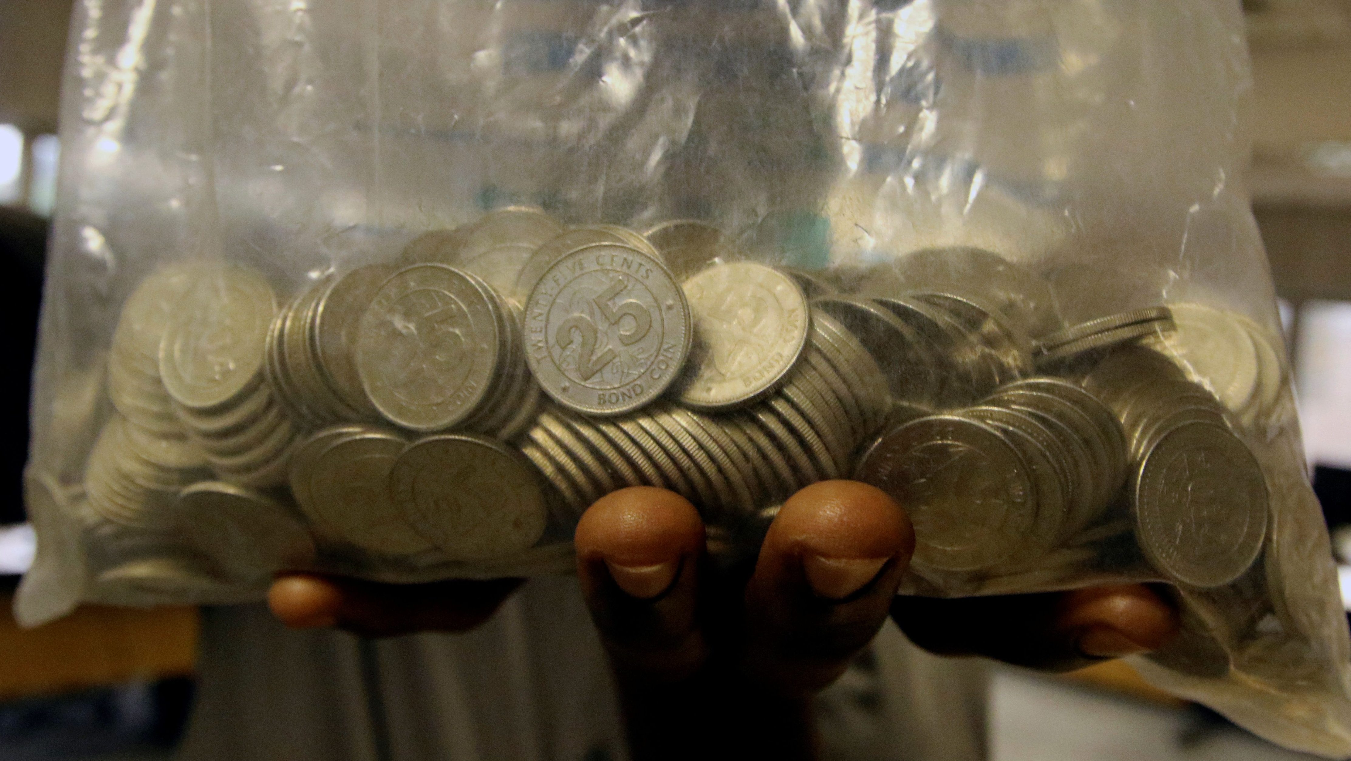 A man holds a bag of bond coins withdrawn from a bank in central Harare