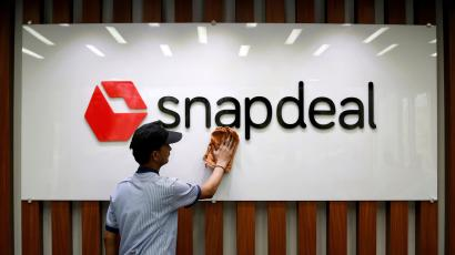 An employee cleans a Snapdeal logo at its headquarters in Gurugram