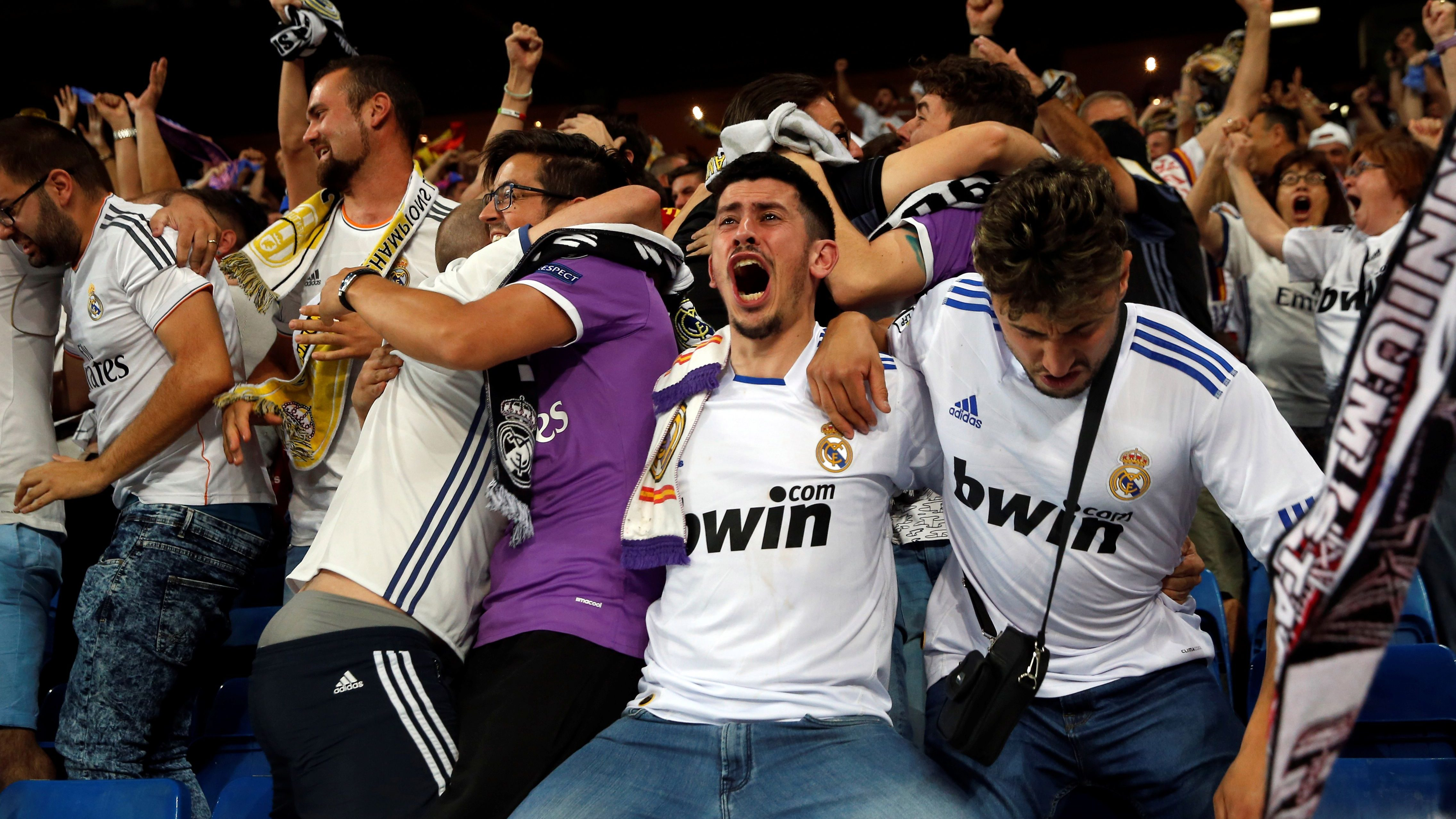 Football Soccer- Juventus v Real Madrid - UEFA Champions League Final - Santiago Bernabeu Stadium, Madrid, Spain - 3/6/17 Real Madrid fans celebrate a goal as they watch the Champions League final match on giant TV screens. REUTERS/Susana Vera - RC13102076B0