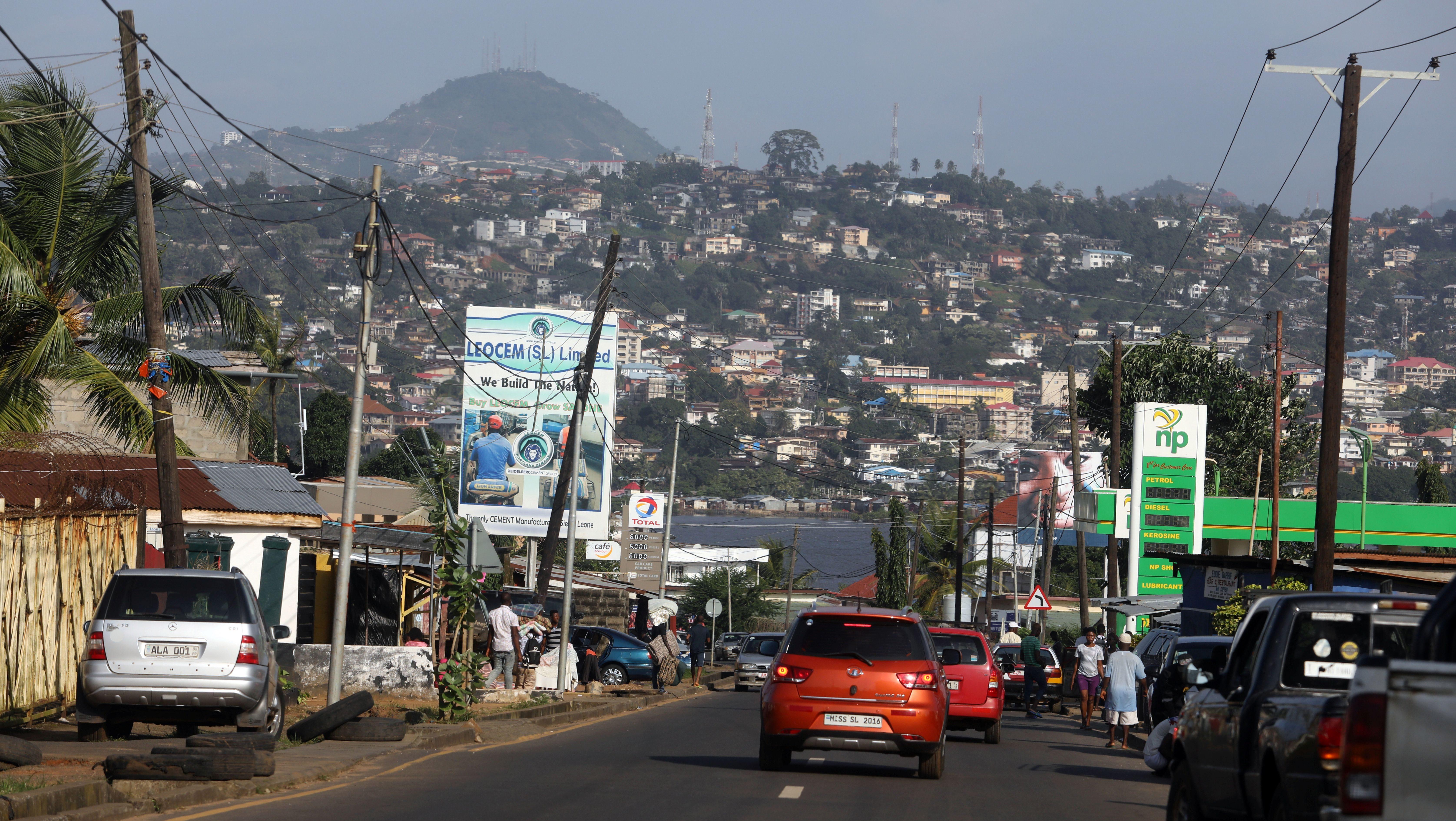 Cars are seen driving down a street in Aberdeen neighborhood of Freetown