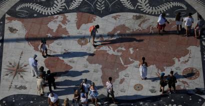 People take pictures at a square decorated with a giant world map in Lisbon