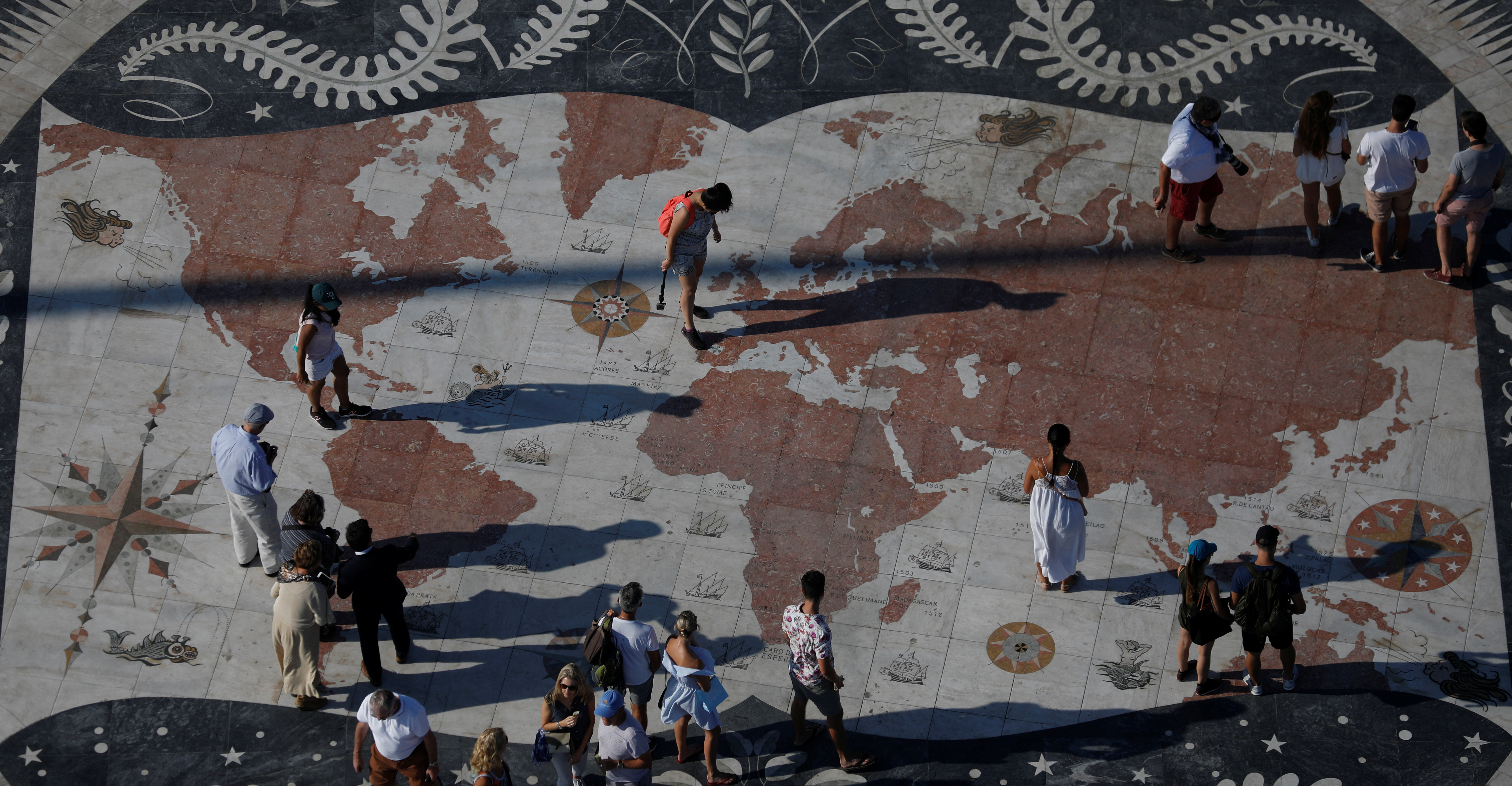 People take pictures at a square decorated with a giant world map in Lisbon, Portugal September 6, 2017.