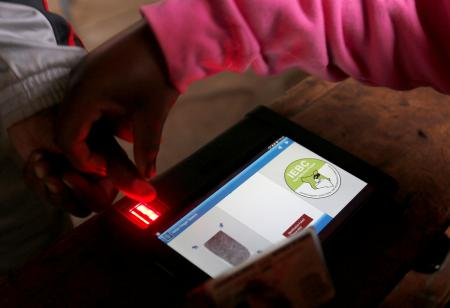 An IEBC official uses an electronic voter identification machine to check a voters' status at a polling station during a presidential election re-run in Nairobi, Kenya October 26, 2017.