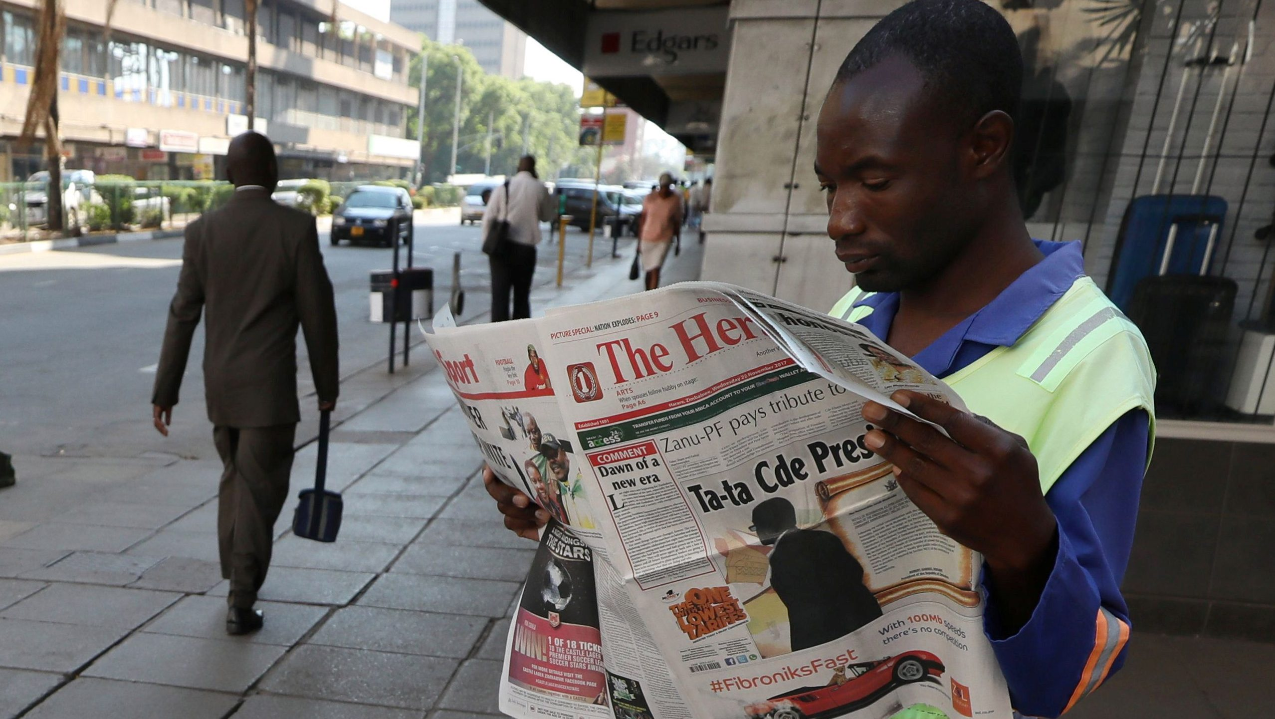 A Zimbabwean vendor reads a newspaper after President Mugabe resigned in Harare