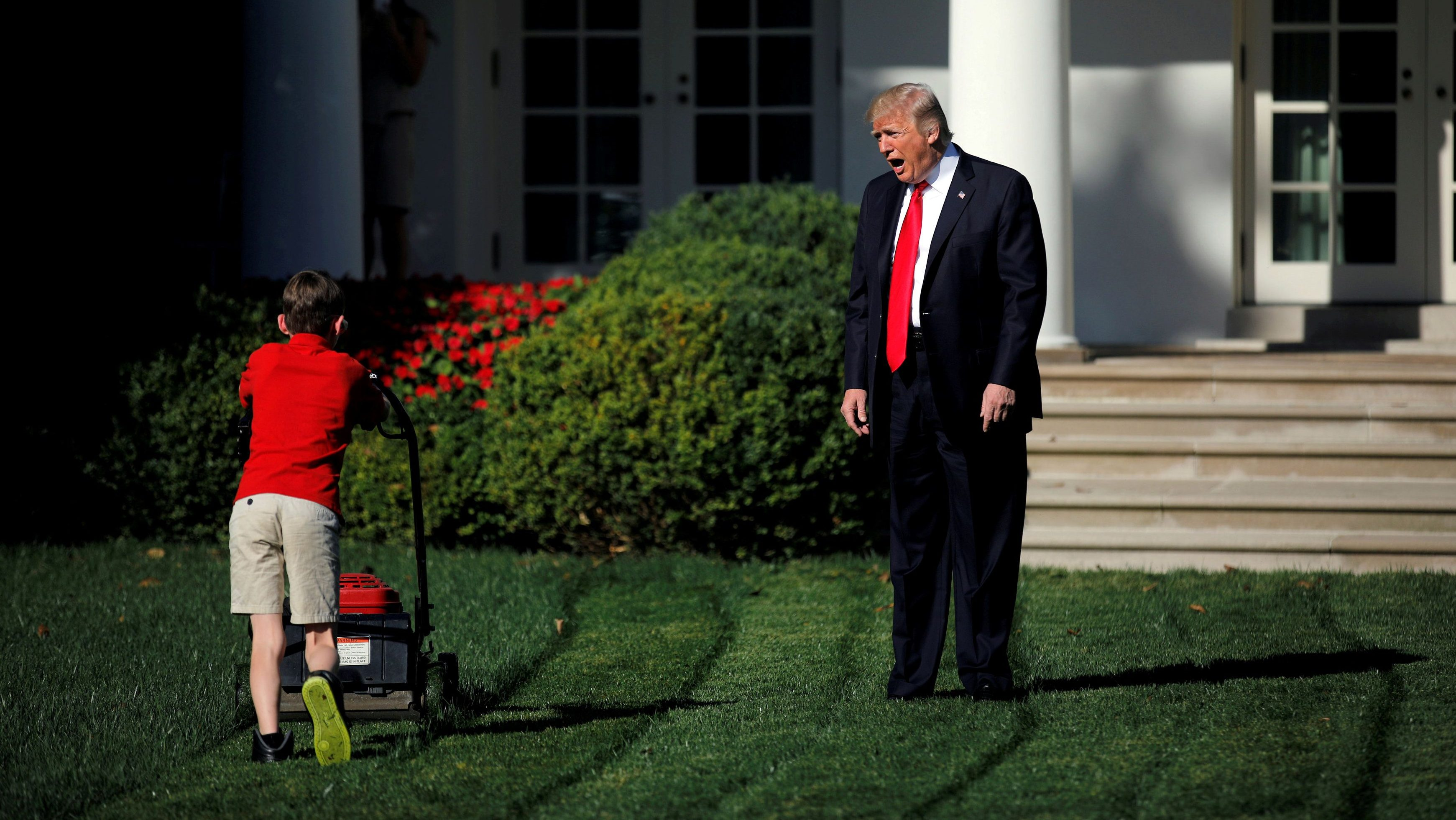 """U.S. President Donald Trump welcomes 11-year-old Frank Giaccio as he cuts the Rose Garden grass at the White House in Washington, U.S., September 15, 2017. Carlos Barria: """"Working in Washington, covering politics, I struggle with the rigid and tightly controlled images we're asked to take. But once in a while I get to witness a natural, unscripted moment. One morning, we were told the White House Pool would gather by the door of the Rose Garden for a photo opportunity. It was unscheduled so I didn't know what to expect. As it happened, the President was planning to surprise 11-year-old Frank Giaccio, who had written a letter to Trump offering to mow the White House lawn. Giaccio had been invited to work for a day at the White House alongside National Park Service staff. As we waited for Trump, I saw that Giaccio was very focused on this job and not paying much attention to the group of journalists, photographers and cameramen milling around the garden. Suddenly, from the other side of a hedge, wearing his signature, long red tie, President Trump appeared, dropping in as if this were an episode of The Apprentice. He walked towards Giaccio to say hi and pose for a picture. He began shouting to the boy above the noise of the lawnmower, but it was too loud. Giaccio was so focused on his job that he didn't notice Trump. He walked right past, pushing the machine. Trump paused for a second and walked to the end of the lawn to talk to Giaccio, but again, he didn't stop mowing. He kept going until his father rushed onto the scene to grab his attention, and he finally stopped to greet Trump. The image of Trump shouting at a kid who is mowing his lawn might have many interpretations in today's politically polarized United States. But for me it was just a kid who loved what he was doing, to the point he almost appeared to ignore the President."""" REUTERS/Carlos Barria/File photo SEARCH """"POY STORY"""" FOR THIS STORY. SEARCH """"REUTERS POY"""" FOR ALL BEST OF 2017 PACKAGES. - RC1DE25540A0"""